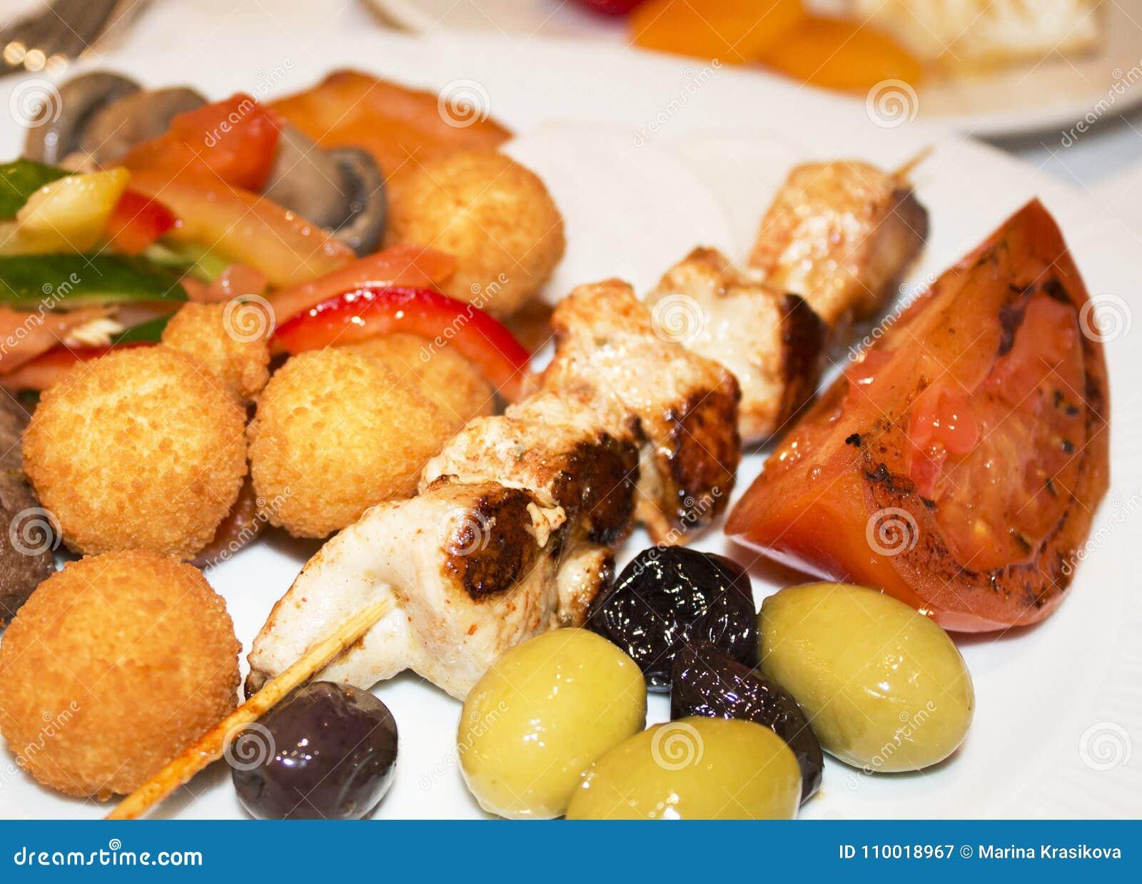 Op een plaat is er een kip shashlik met aardappels, olijven, ol