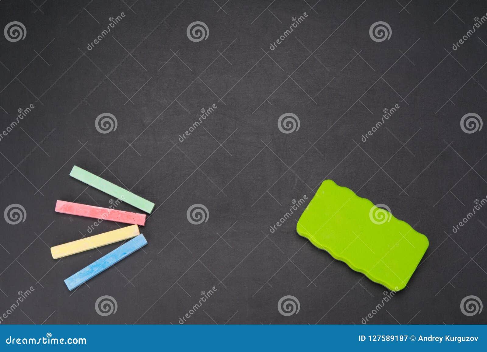 Op een zwarte is de raad een multi-colored krijt voor tekening en een spons voor het wissen