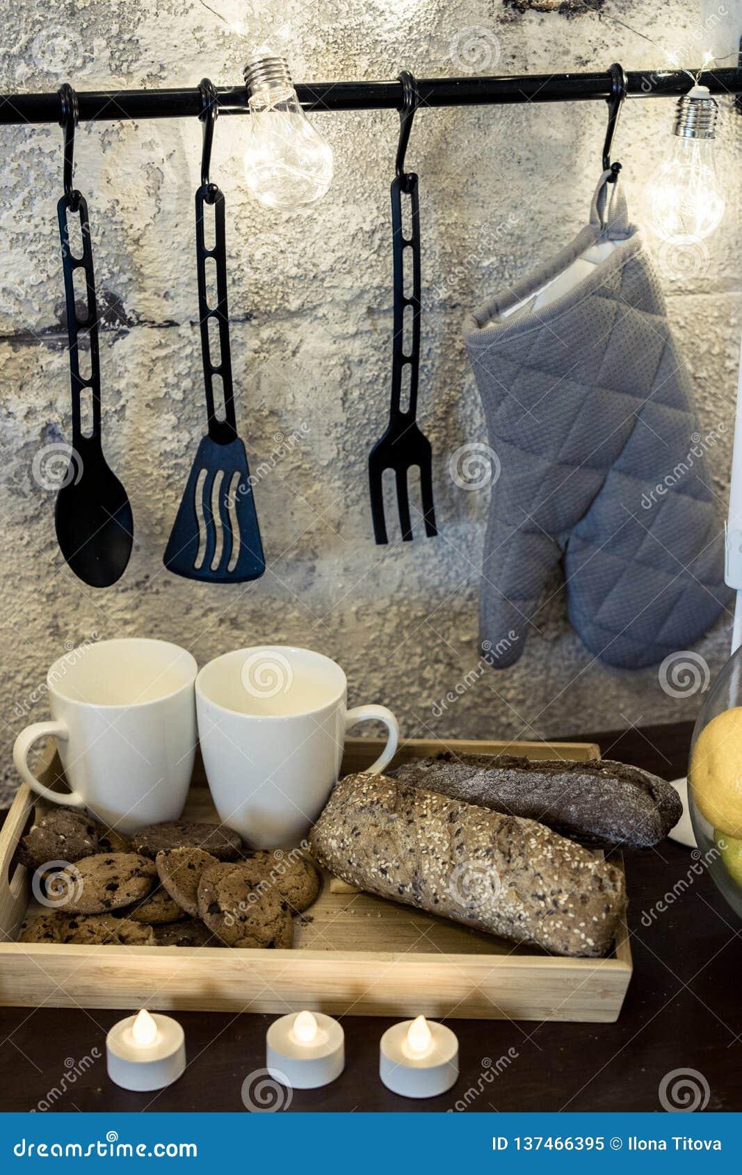 Op keuken is de lijst voor een concrete grijze muur witte fluitjes een slinger hangende pannelap het wachten op valentijnskaart