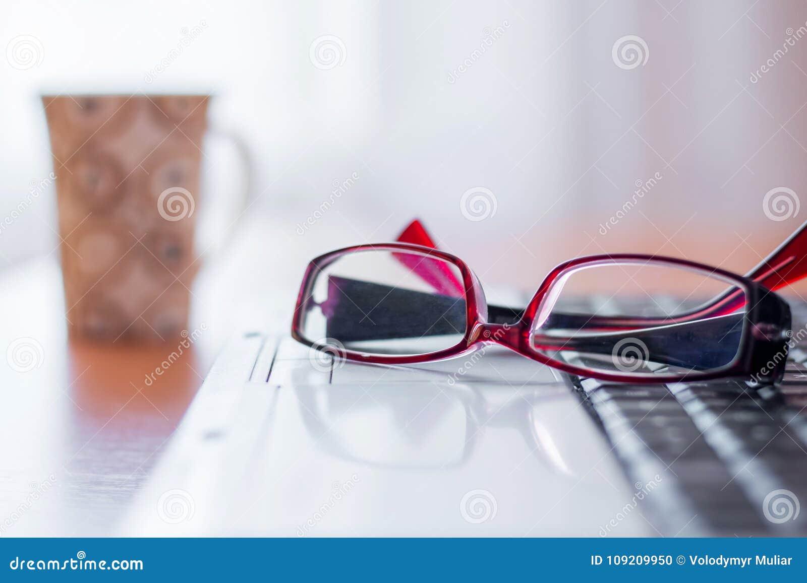 Op laptop lig glazen, verder op de lijst is een kop, in