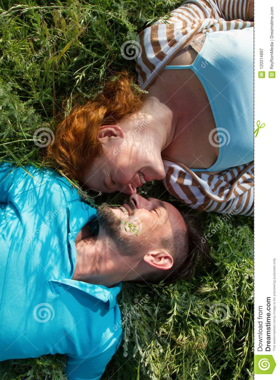 Portrait of happy mature woman and man looking at each other laying on green grass with love. They are relaxing together