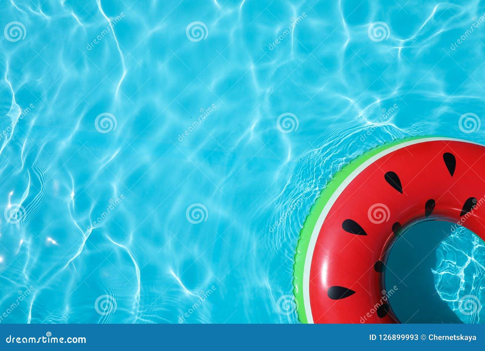 Opblaasbare ring die in zwembad op zonnige dag drijven