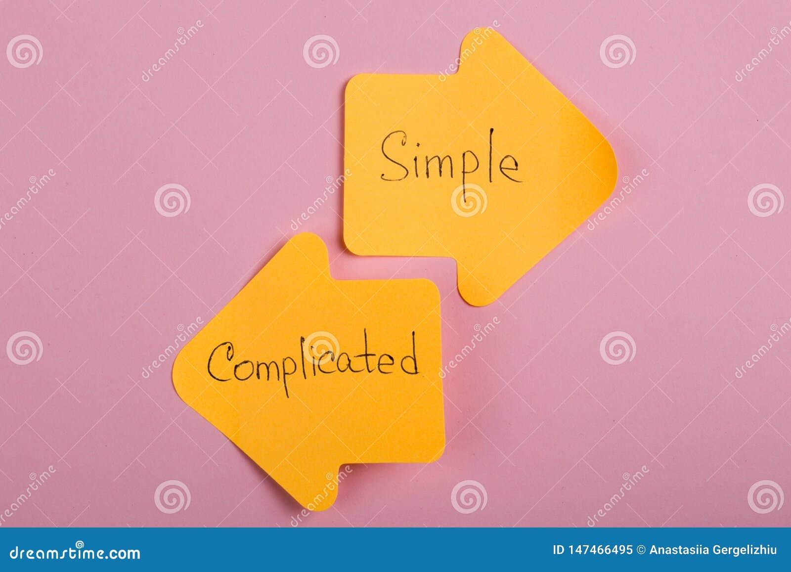 Opci?n de la vida - etiquetas engomadas anaranjadas bajo la forma de flechas del ?ndice con el texto complicado y simple en fondo