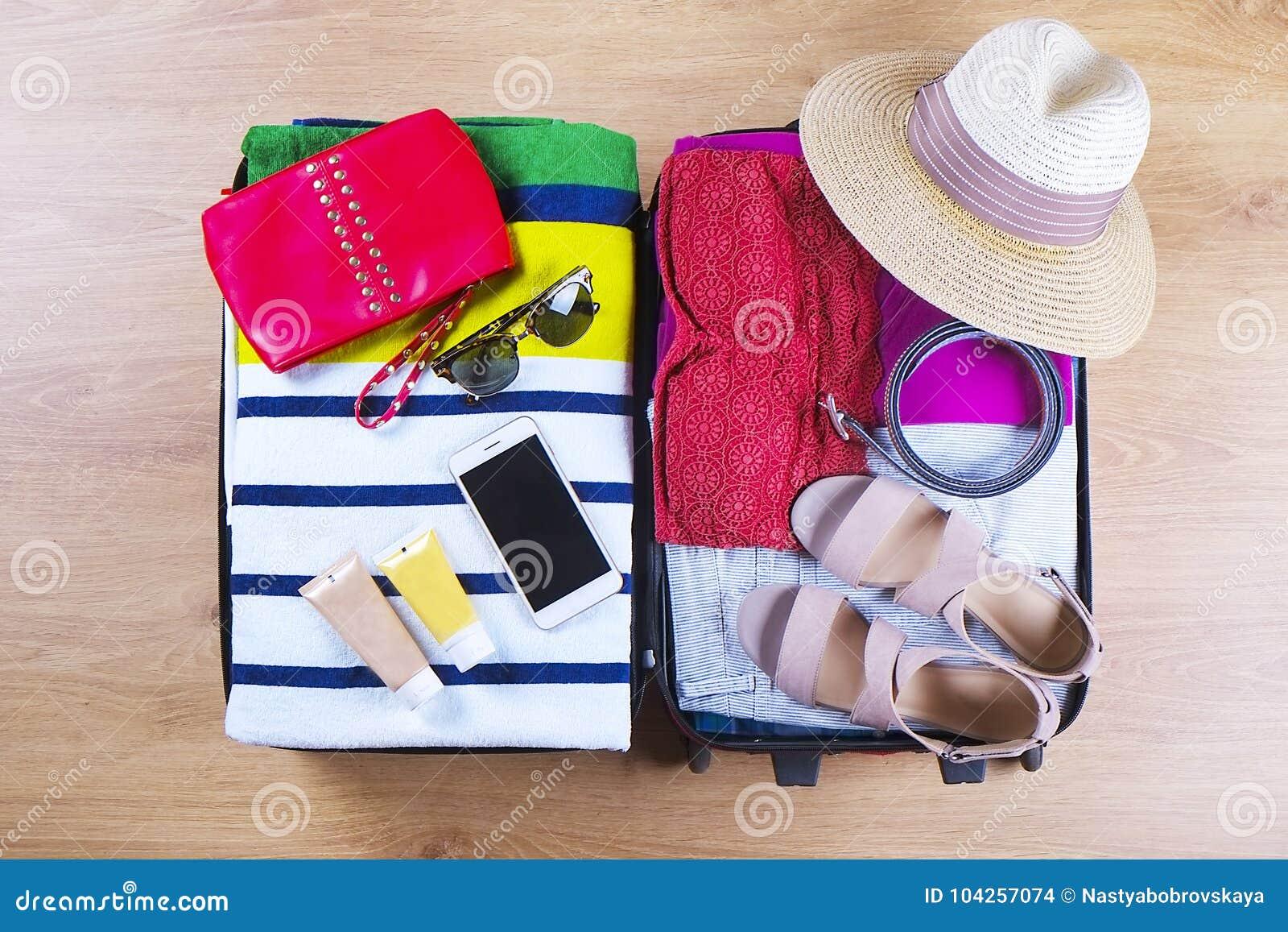 Open упаковал чемодан с женскими одеждами и аксессуарами лета, шляпой, солнечными очками, пляжным полотенцем, солнцезащитным крем