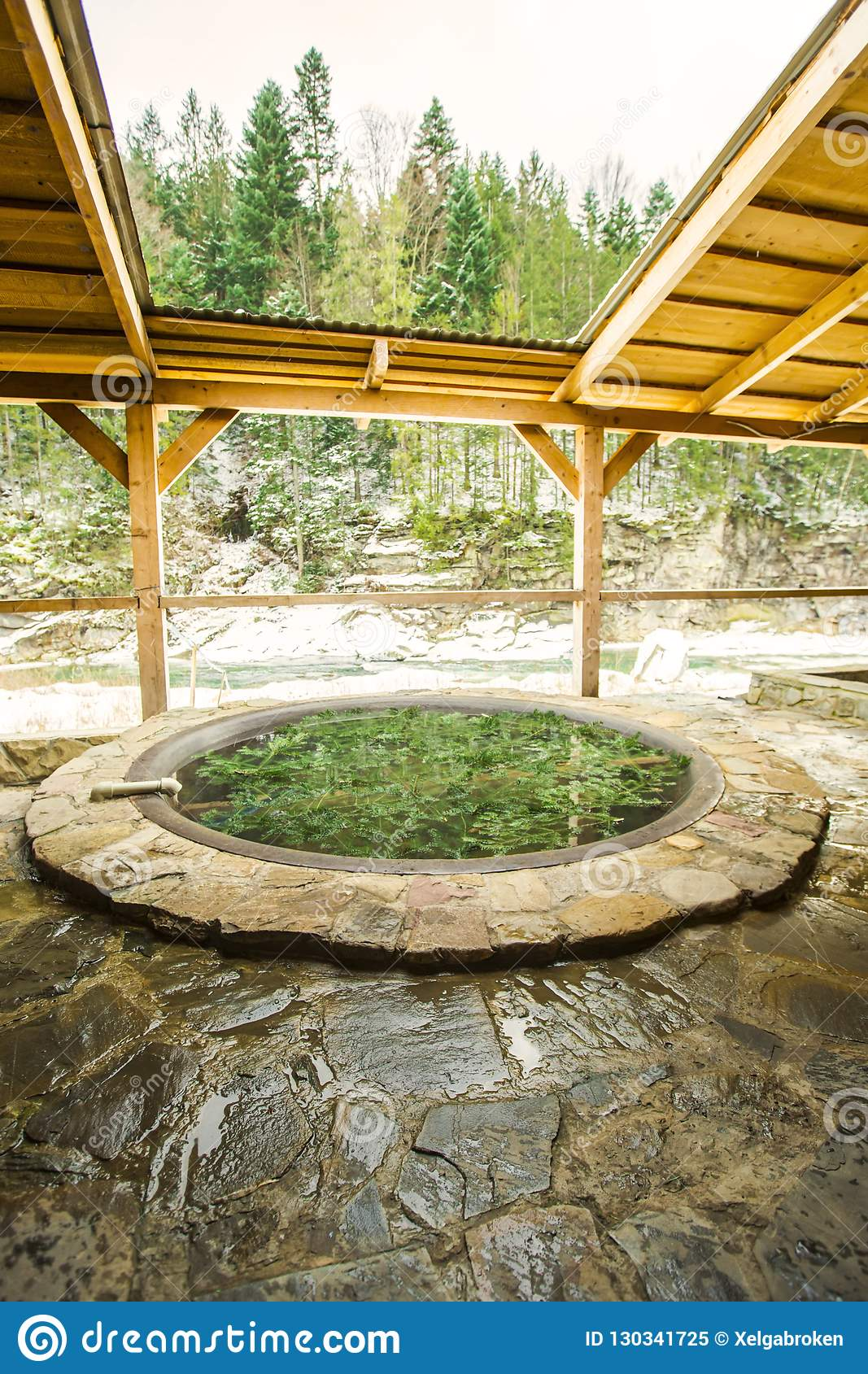 Open air bath outdoors in winter. Iron tub for bathing in hot water