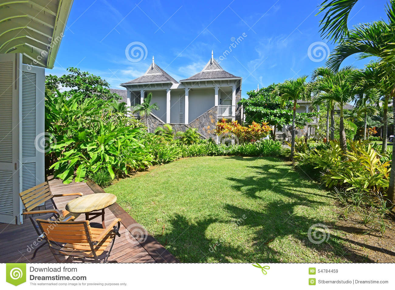 An open air porch with slightly extended roof and tall full length wooden door overlooking beautiful green garden