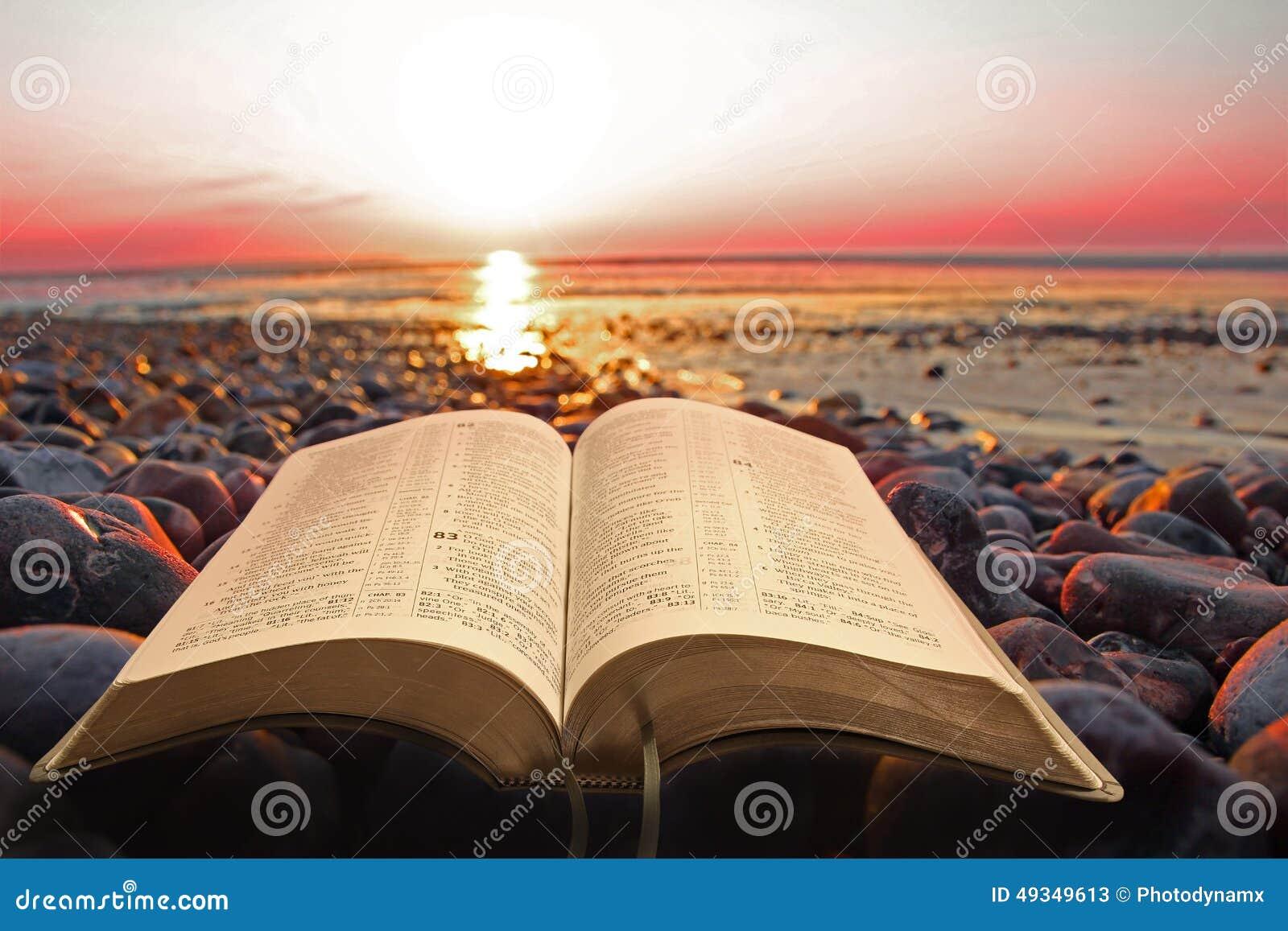 open bible spiritual light on seashore stock photo   image