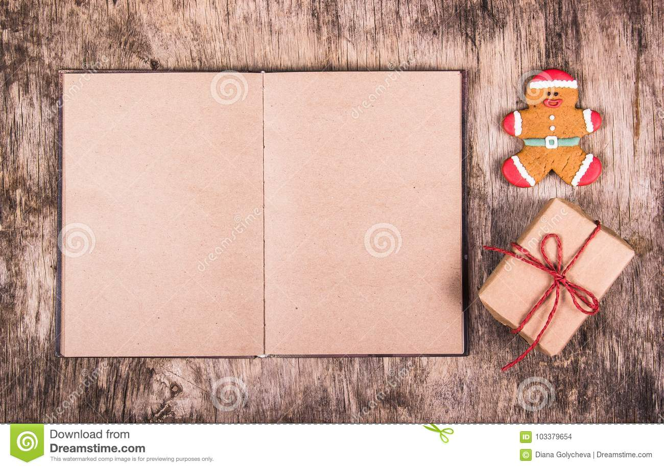 Open book, gingerbread man and gift box. Christmas surprise. Festive backgrounds.