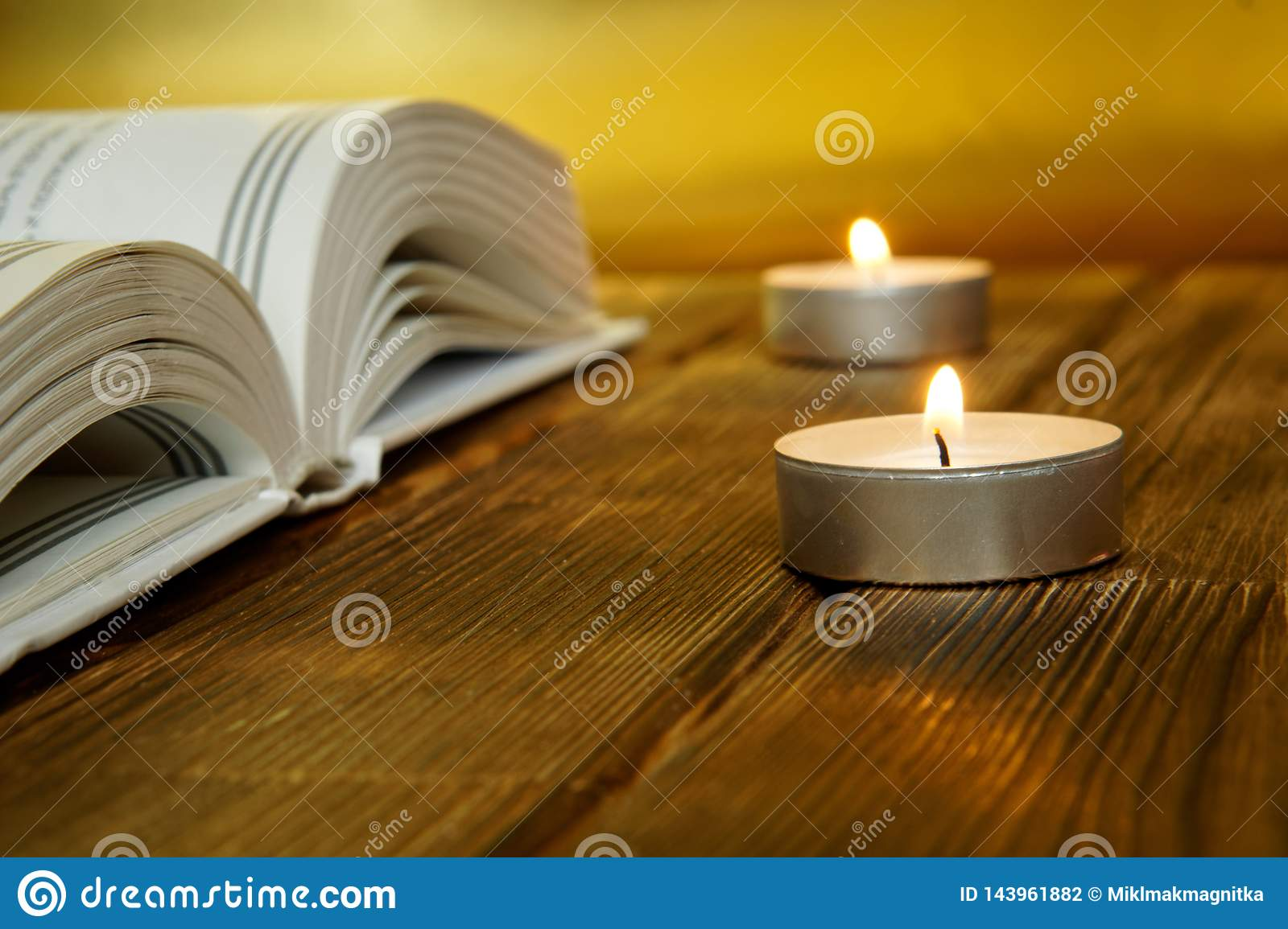 An open book about religion and faith lies on wooden planks on a golden background. Nearby are lit candles