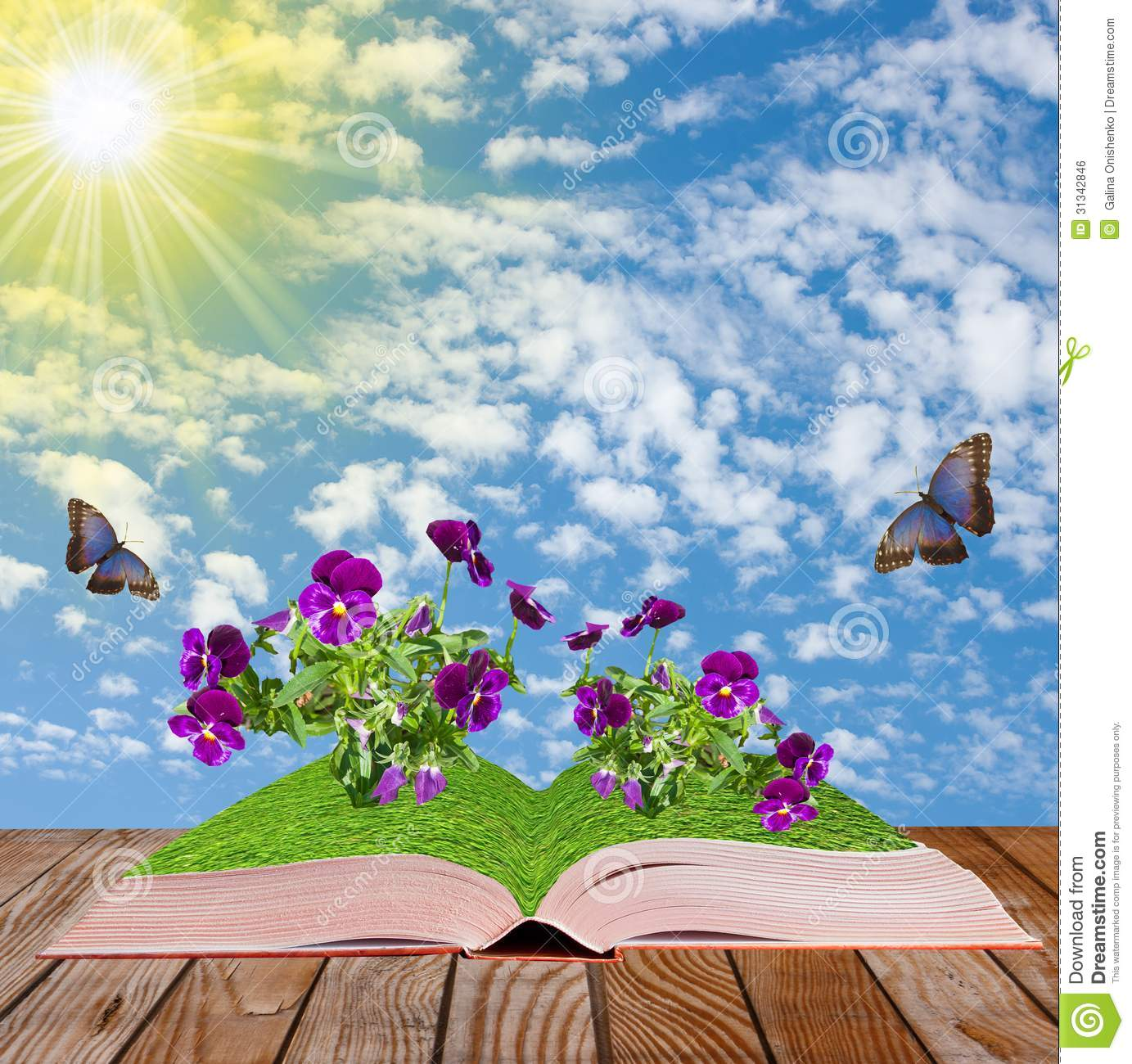 Open book on a wooden surface on a light green background with flowers ...