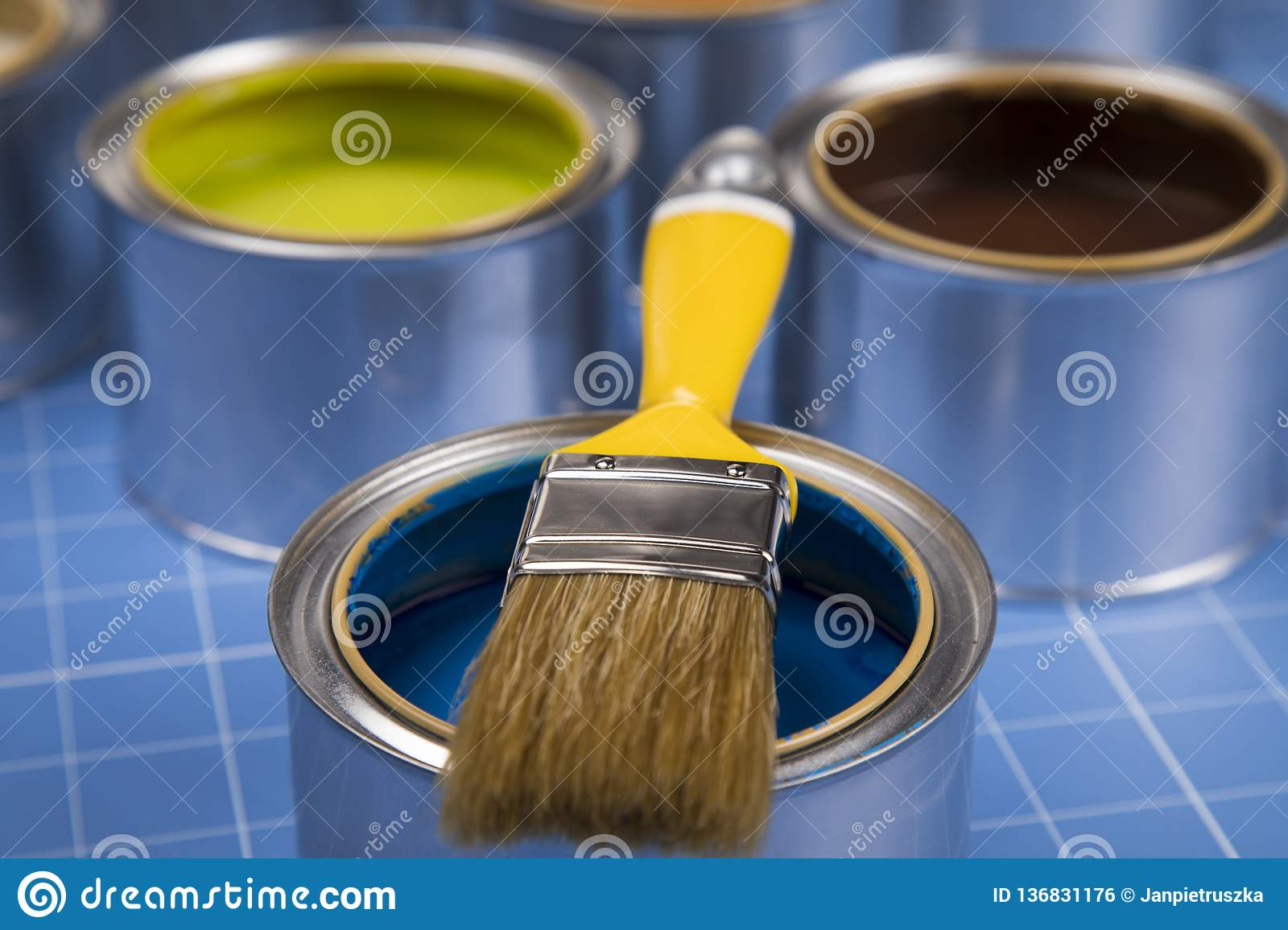 Open cans of paint,Brush, blue background