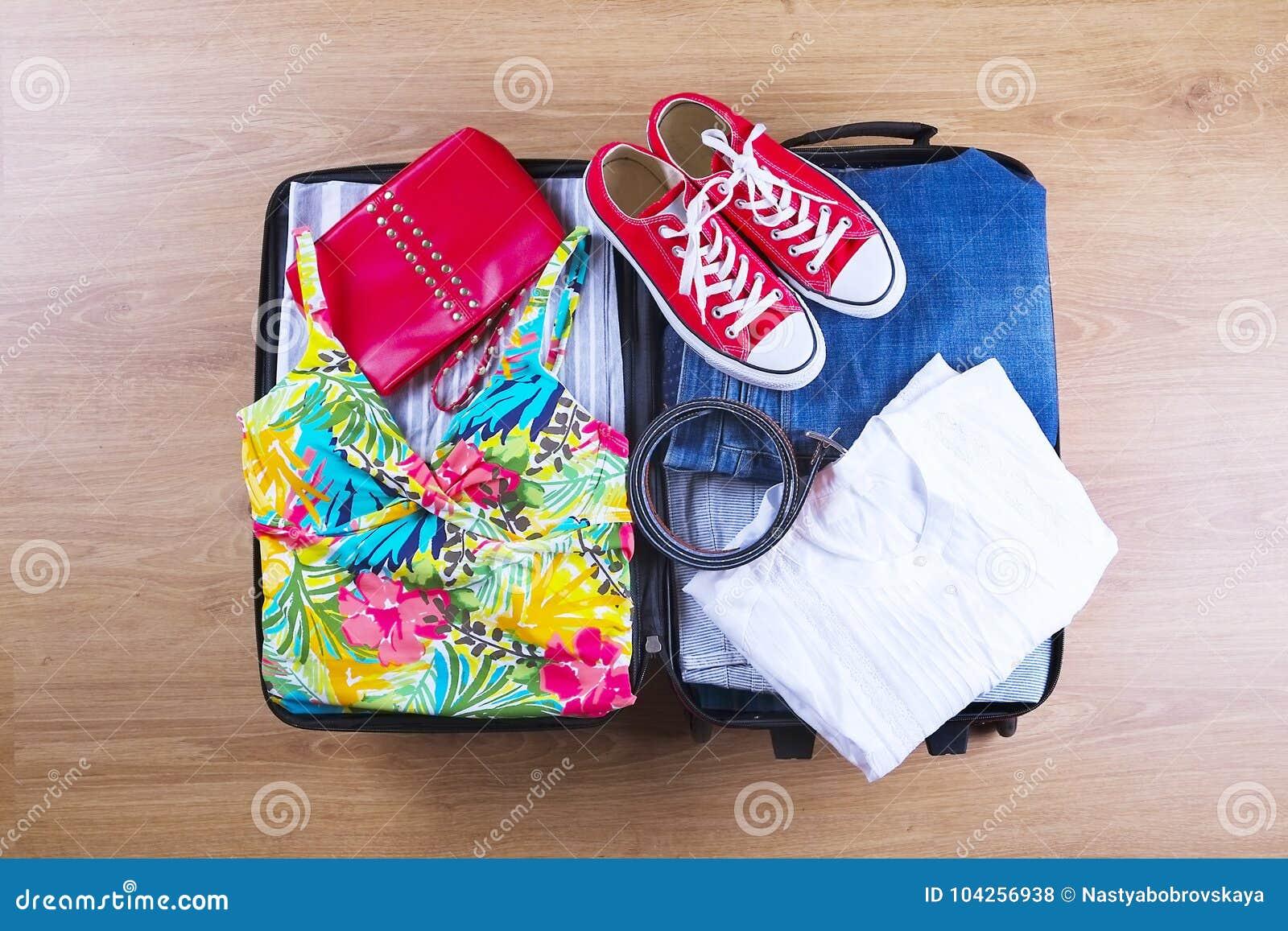 Open a emballé la valise avec les vêtements d été et les accessoires femelles, maillot de bain, les espadrilles, chemise blanche