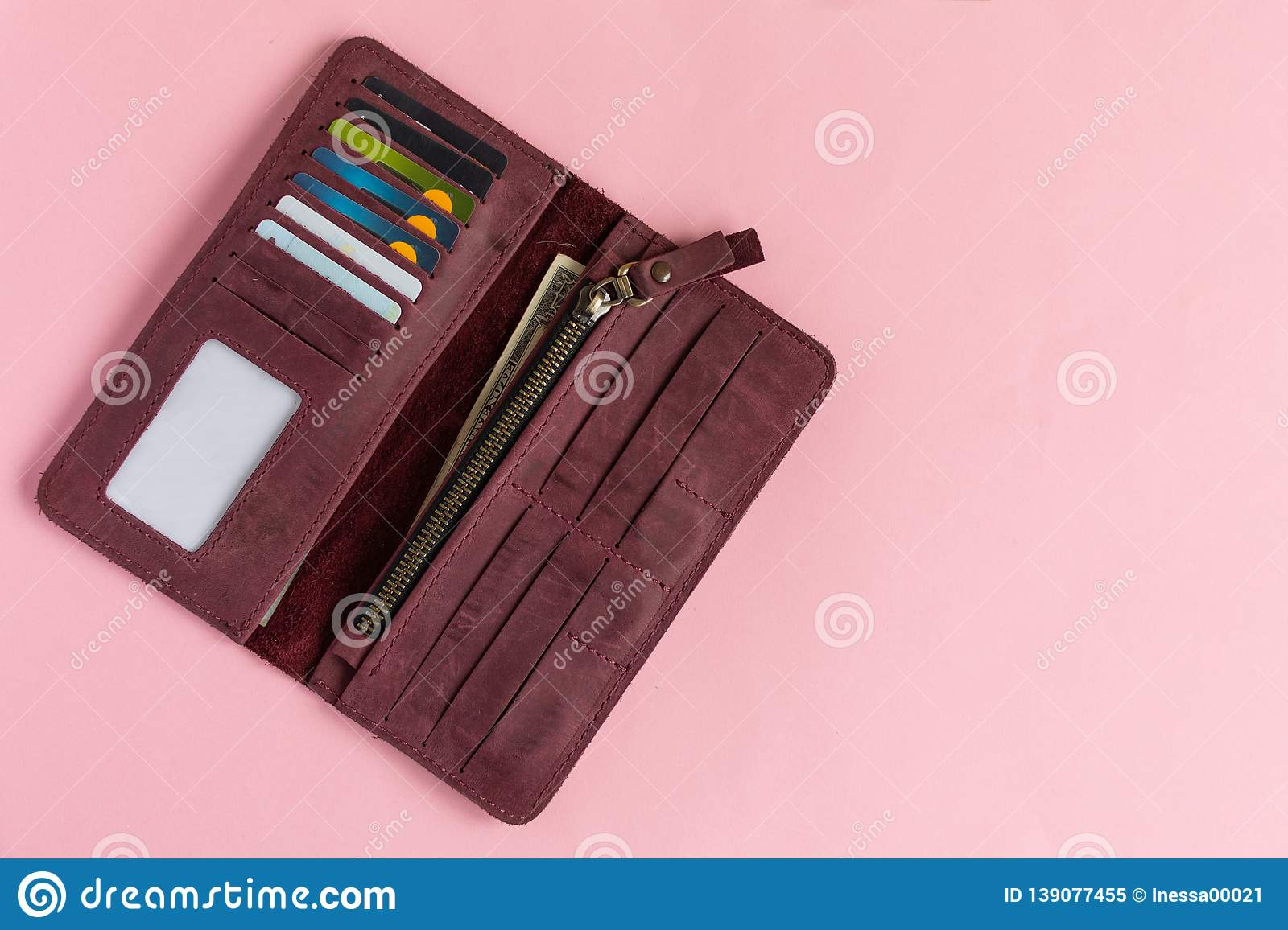 Open female wine-colored wallet with money and credit cards on pastel pink background