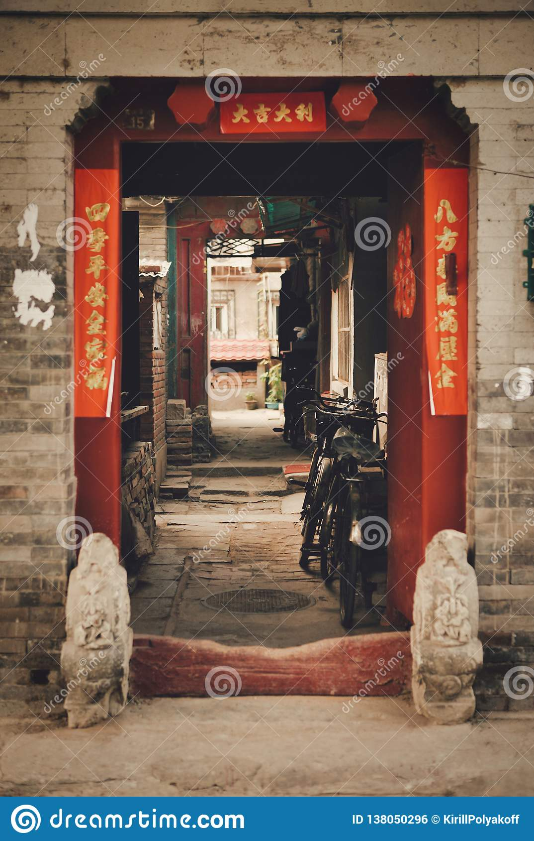 Open gates to Hutong. A sign on both sides of the entrance reads `Welcome`, as well as a wish for happiness and good luck at home.