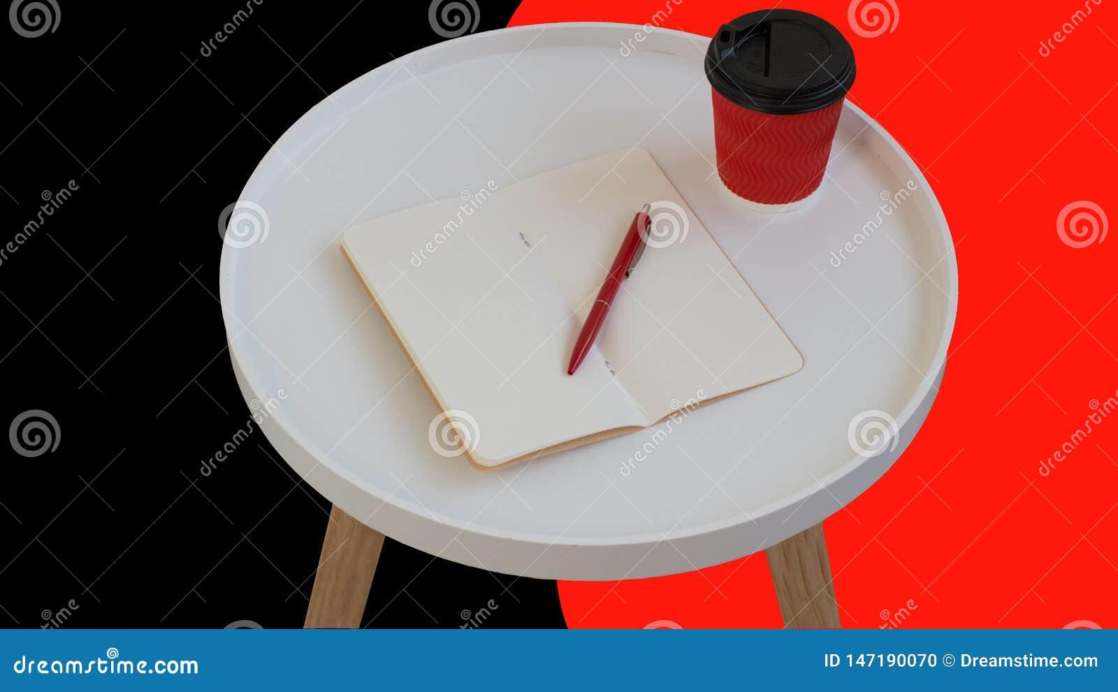 Open leeg leeg notadocument met rode pen, rode kartonkop van koffie om op witte ronde ge?soleerde dagboek houten lijst te gaan
