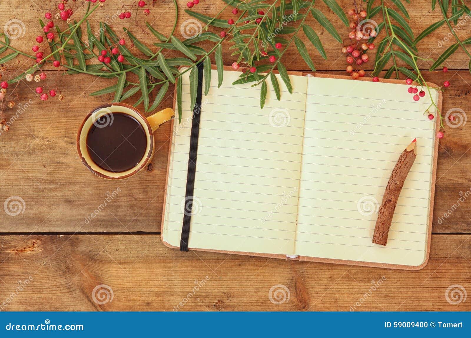 Open leeg uitstekend notitieboekje en houten potlood naast hete kop van coffe over houten lijst klaar voor model retro gefiltreer