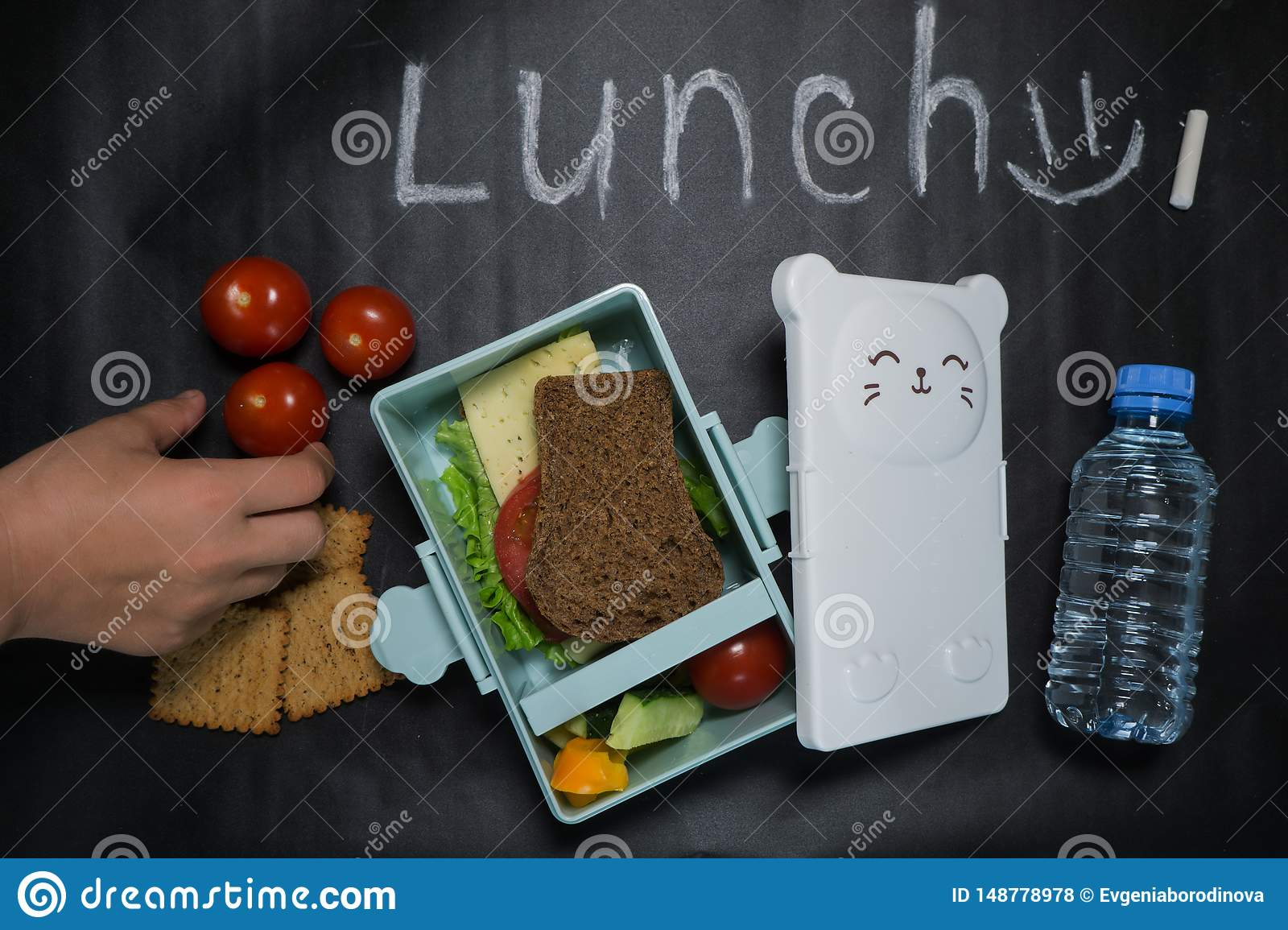 Open lunch box with a sandwich of whole grain bread, cheese, green salad, tomato, cucumber and a bottle of water on a black