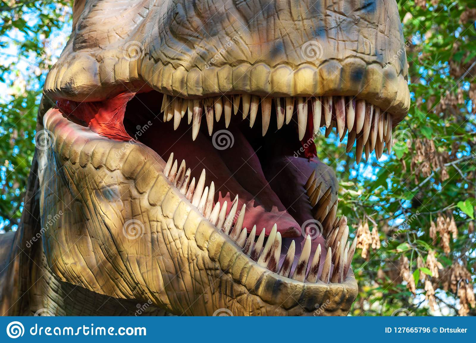 The open mouth of a tyrannosaur with huge sharp teeth