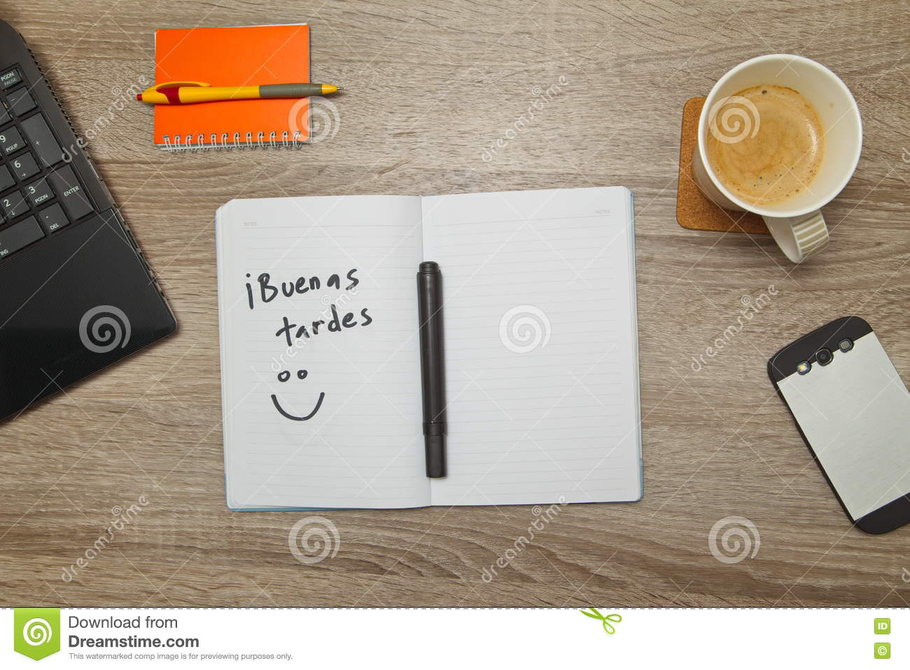 Open notebook with Spanish words `Buenas Tardes` Good Afternoon and a cup of coffee on wooden background.