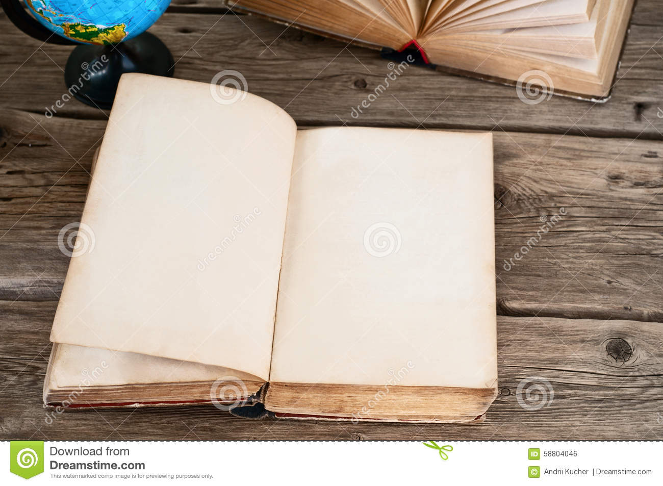 Open old book with blank pages on wooden table globe