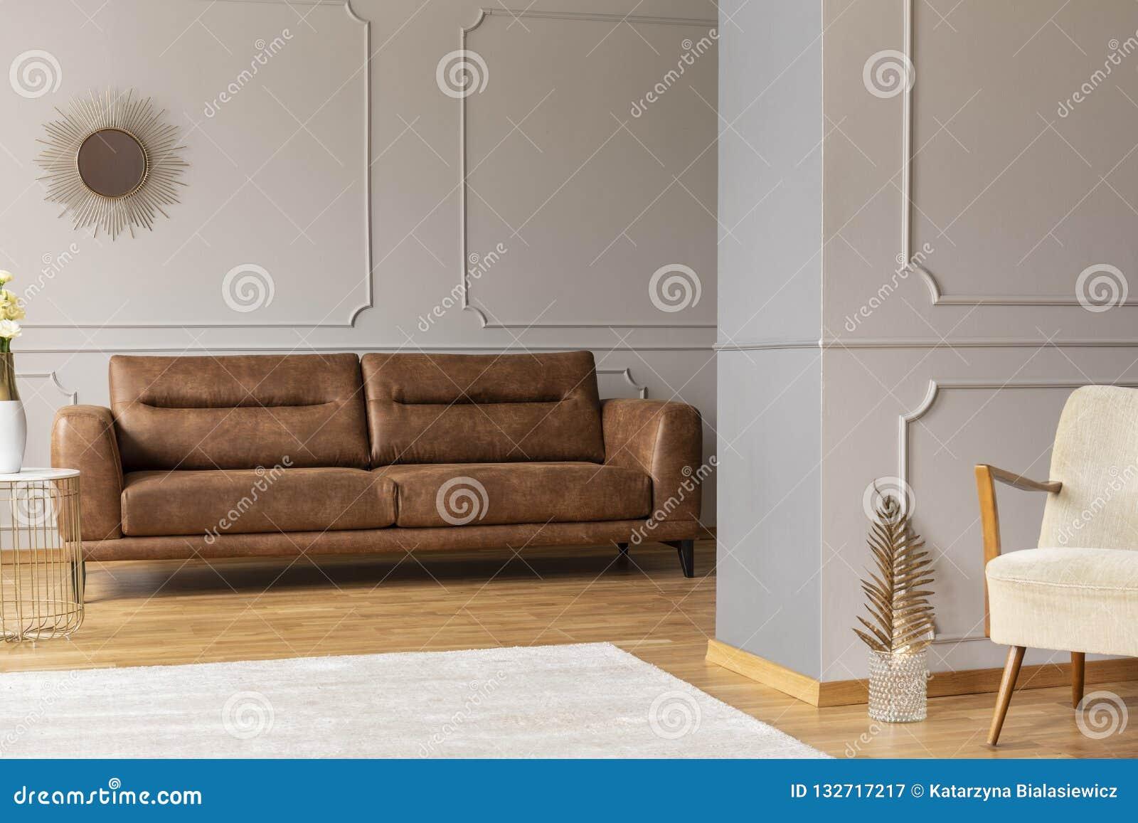 Open plek vlak binnenlands met leer bruine laag, die op muren, wit tapijt en gouden decor vormen