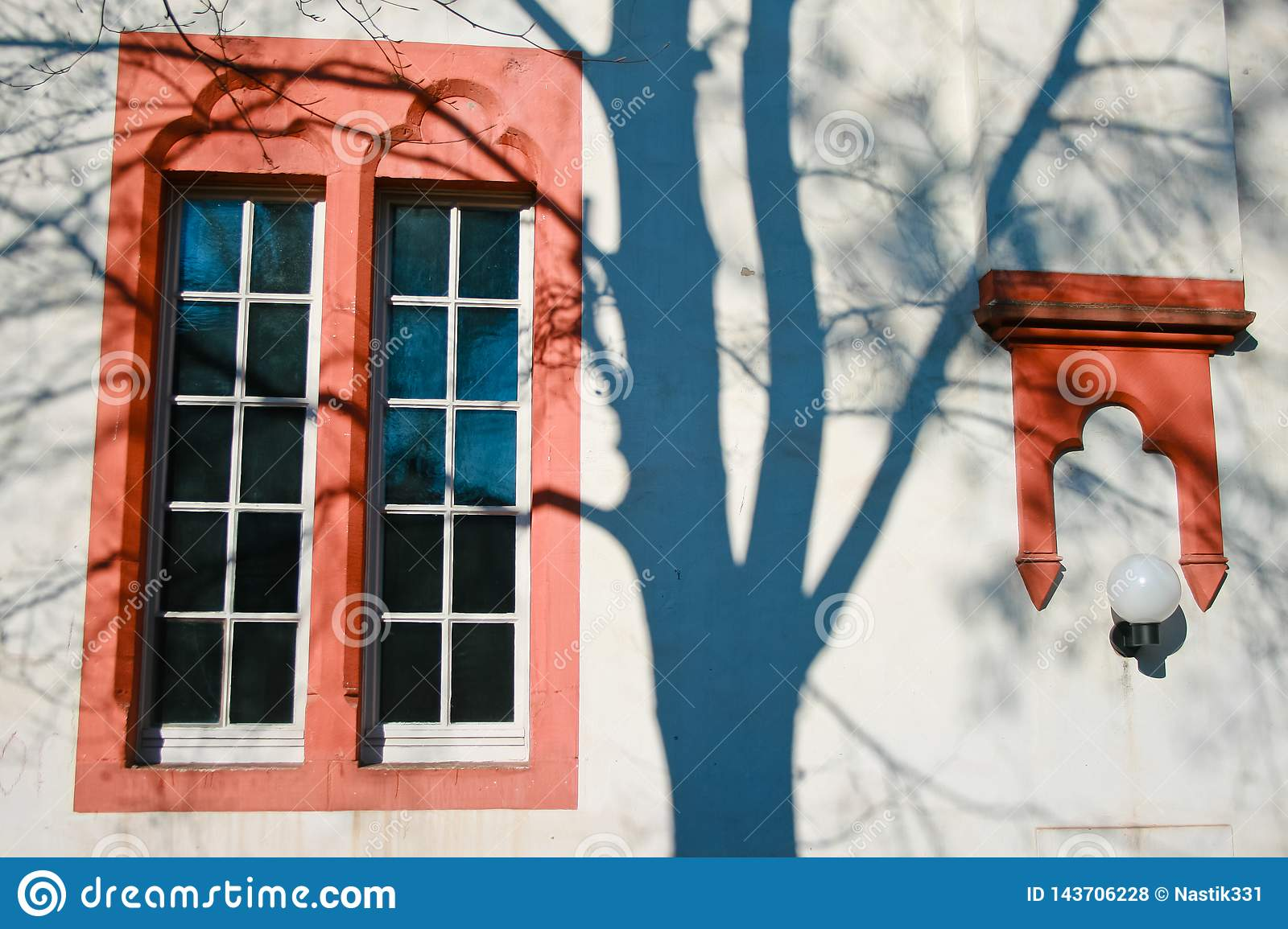 Open red painted window shades of a tree on the wall
