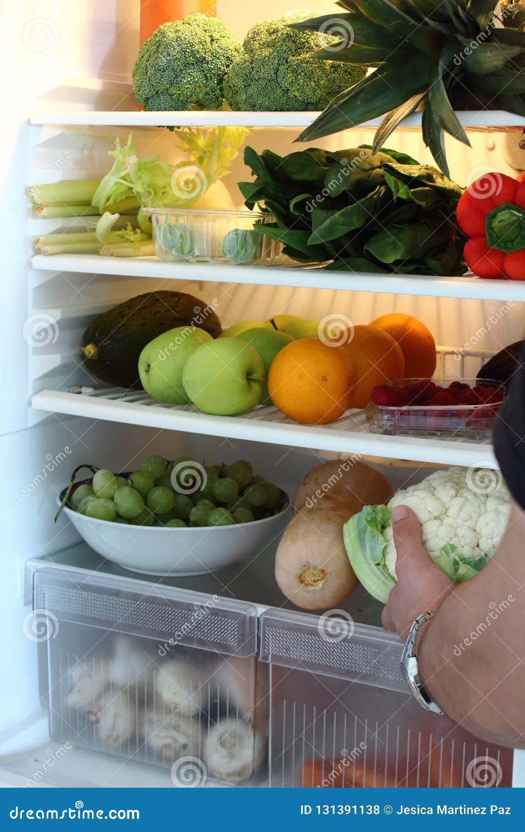Open refrigerator full of healthy vegetarian food.