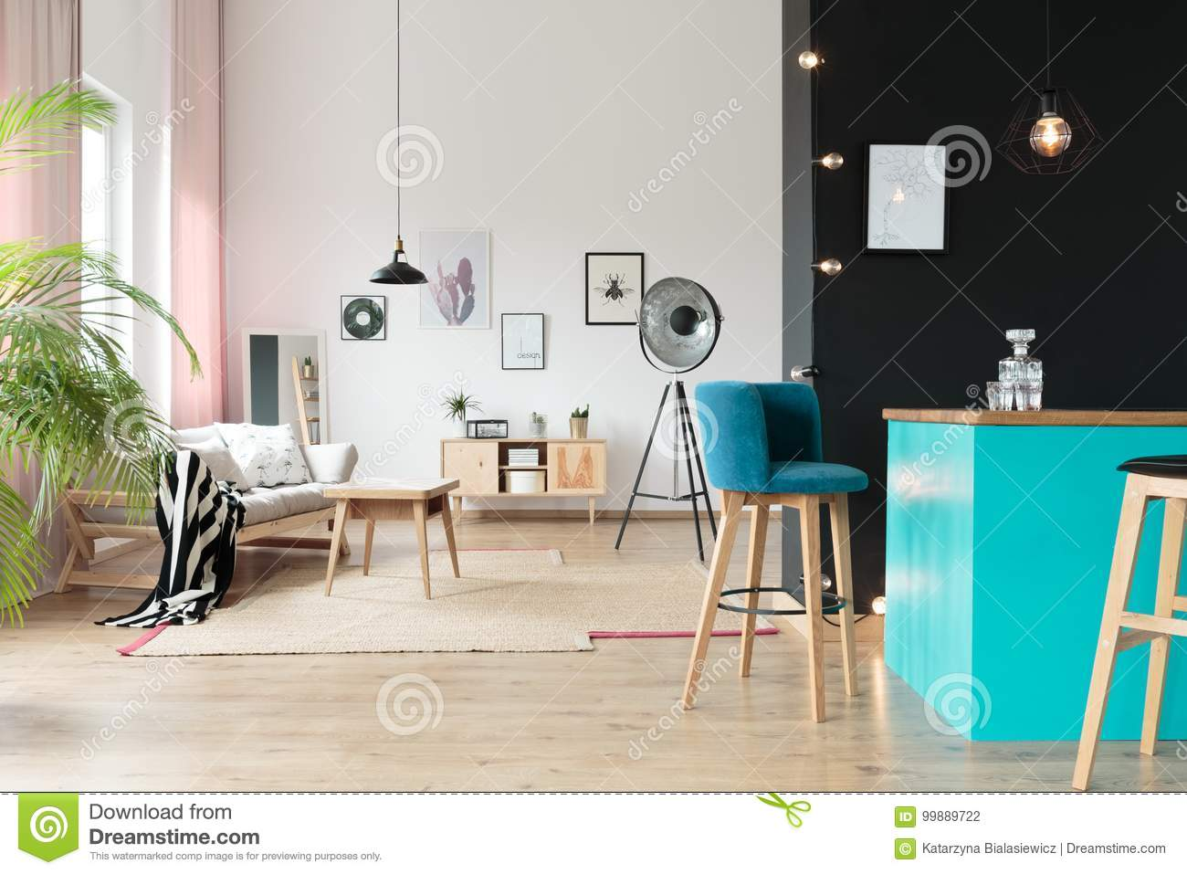 Designer Lamp In Open Relax Space With Suede Barstool At Blue Minibar Against Black Wall