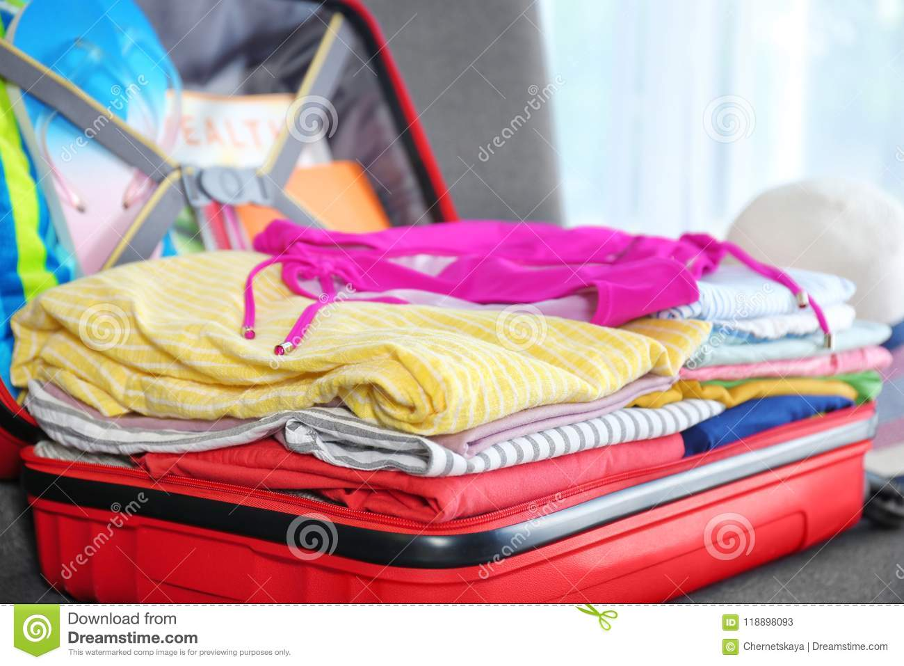 suitcase with different clothes and accessories closeup packing
