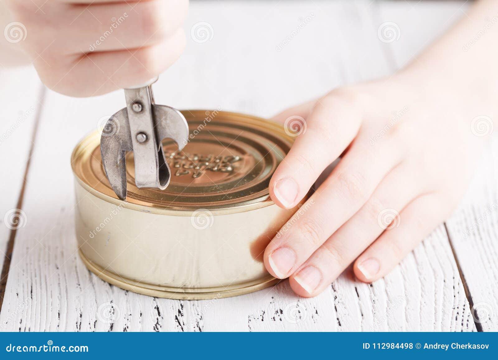 Open tinacan with knife, close up