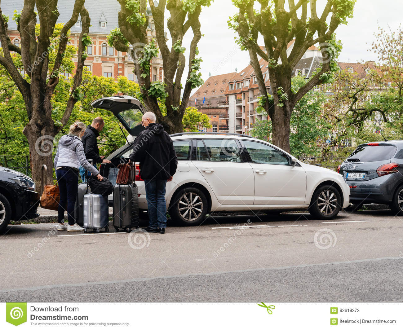 Open trunk people putting luggage in large trunk