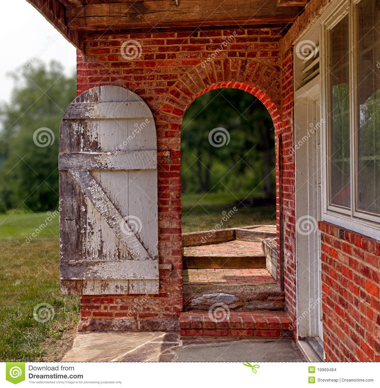 Open Wooden Door In Brick Wall To Garden Stock Photo