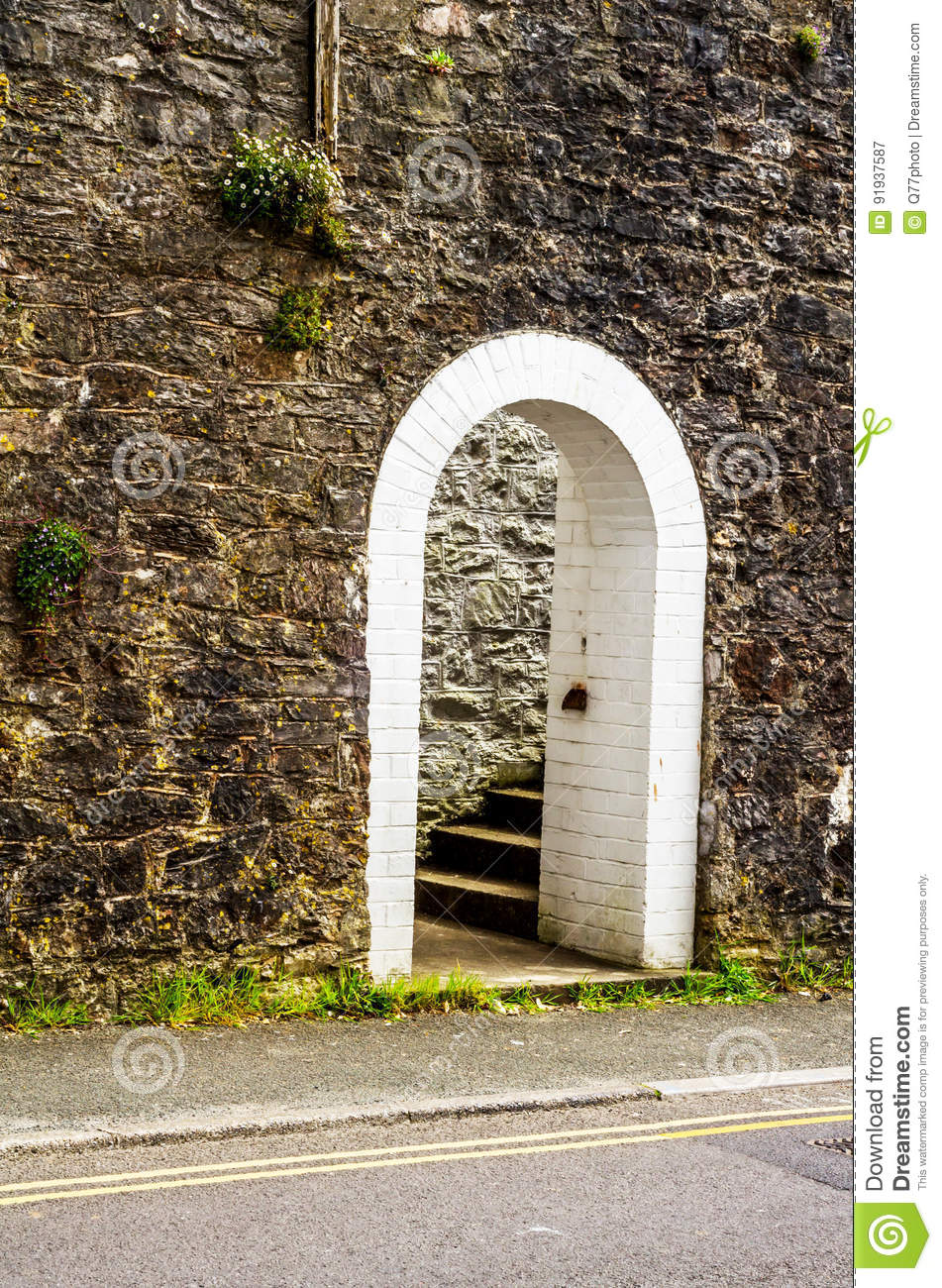 Open wooden door with pointed gothic arch on a white stone wall