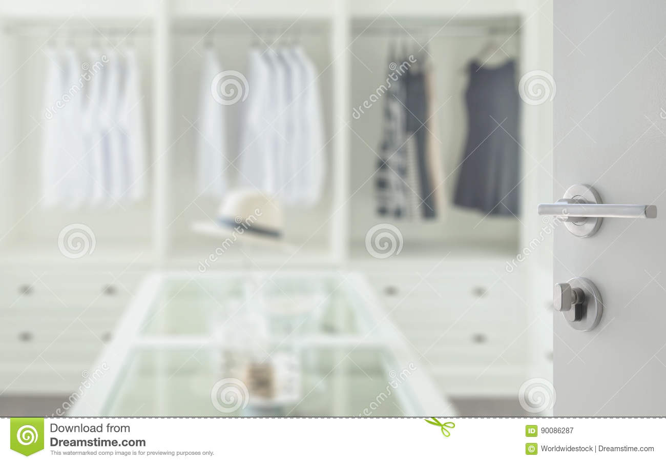 Opened white door to walk in closet room with dresser table