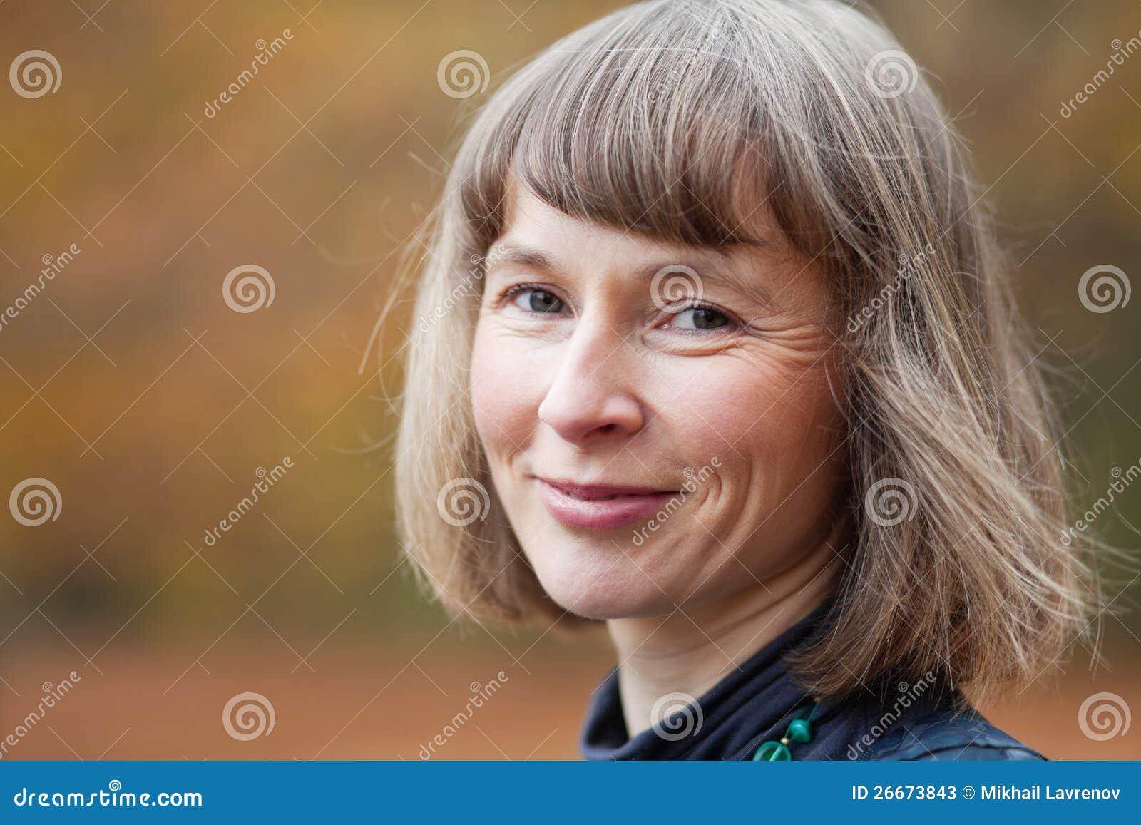 Openlucht portret van glimlachende midden oude vrouw