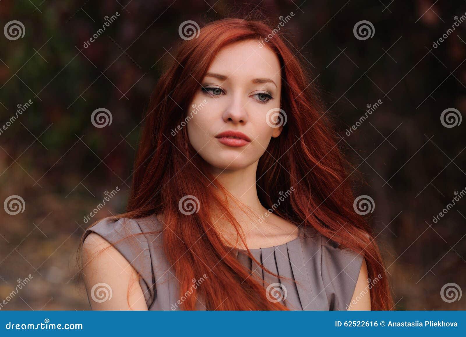 In openlucht portret van mooie jonge vrouw met rood haar