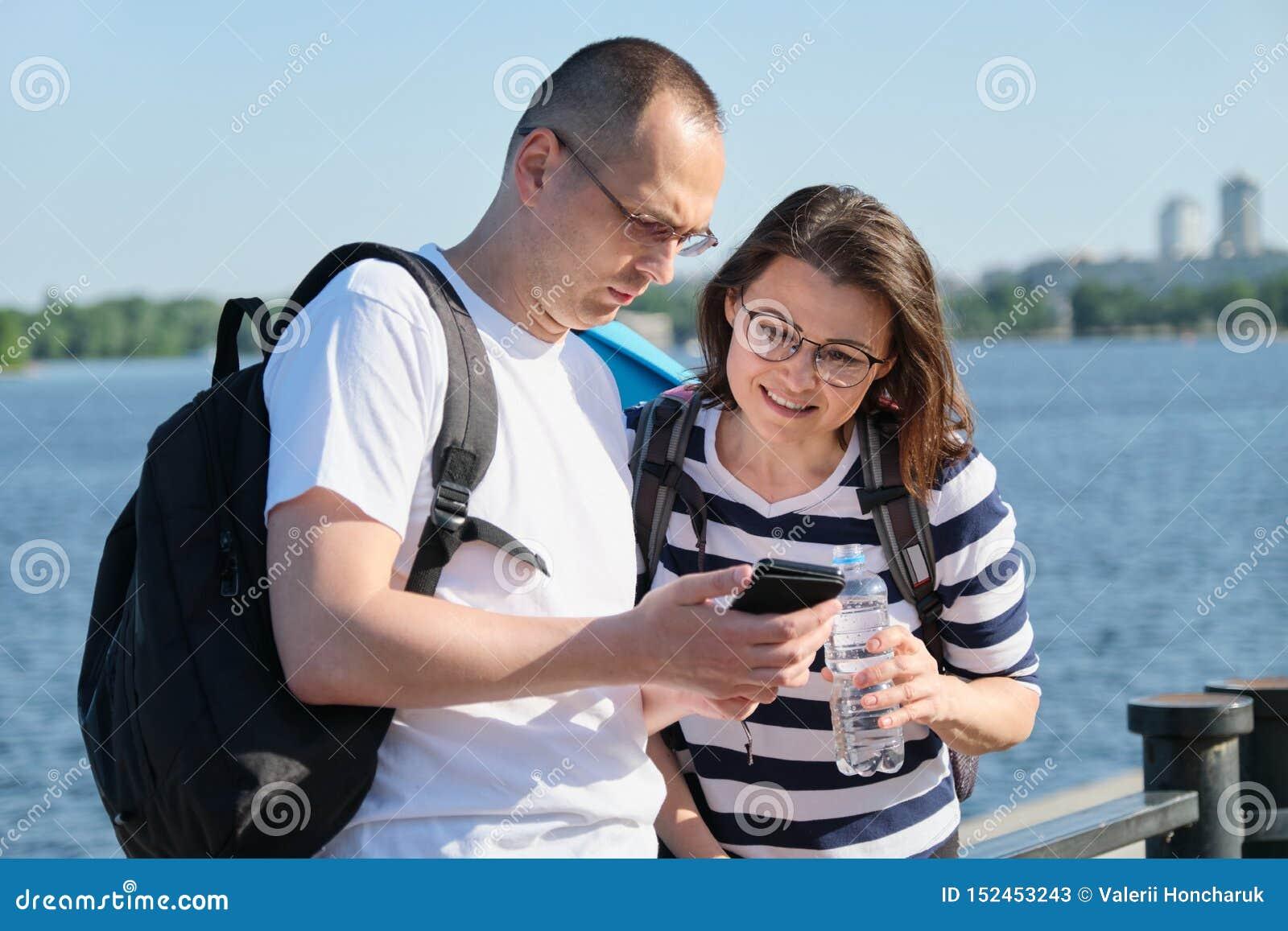 Openlucht rijp paar die smartphone, man en vrouwen spreken gebruiken die in het park lopen