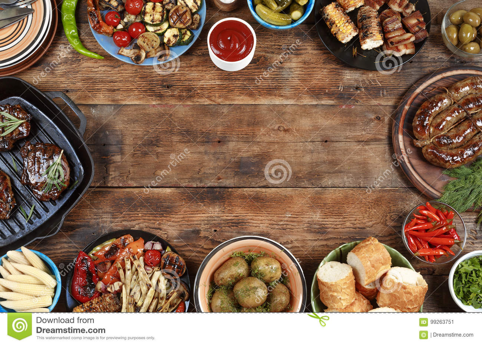 In openlucht voedselconcept Heerlijk geroosterd lapje vlees, worsten en geroosterde groenten op een houten picknicklijst met exem