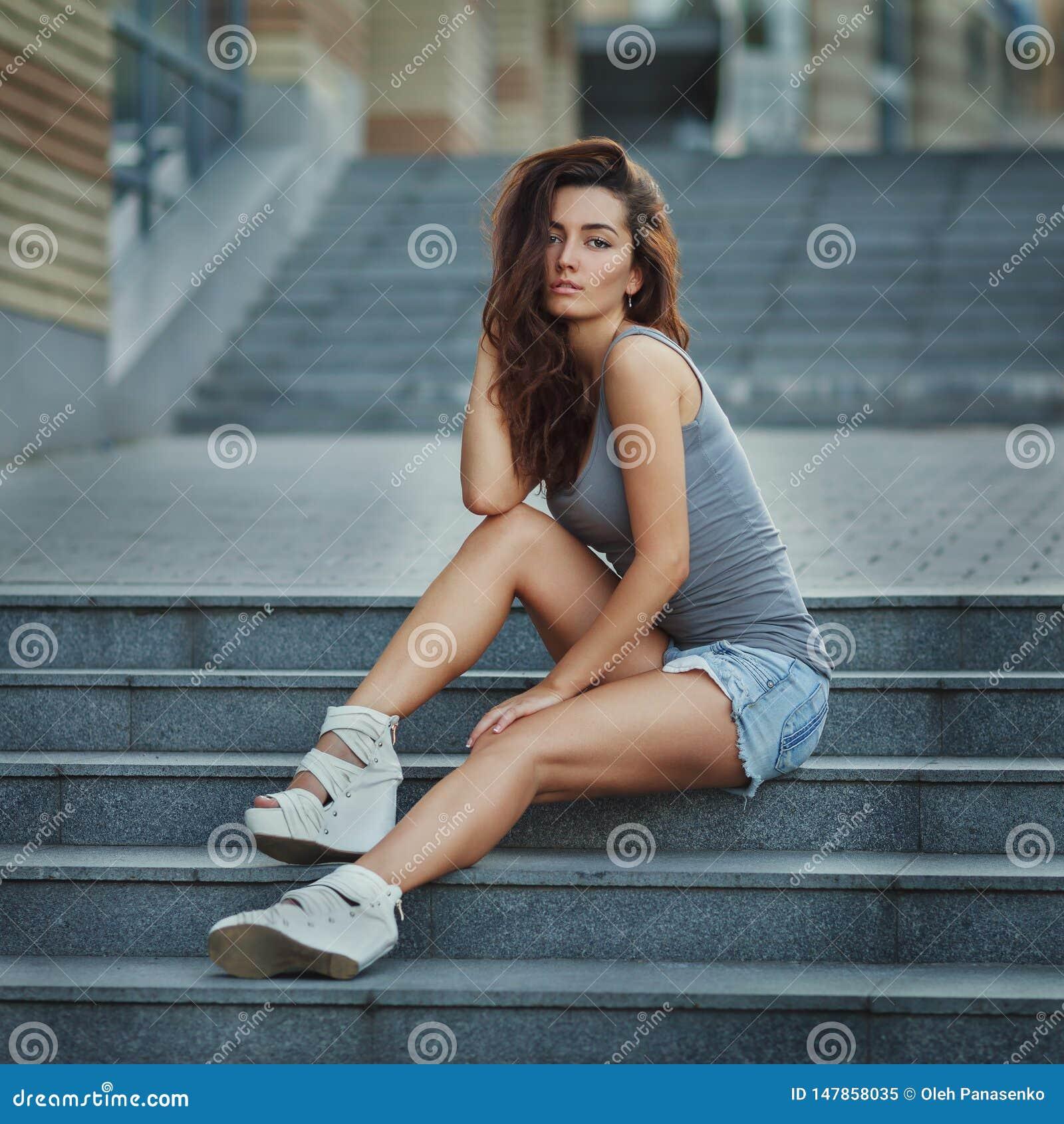 Openluchtlevensstijlportret die van vrij het jonge meisje stellen op trap, in hipster stedelijke stijl dragen op stedelijke achte