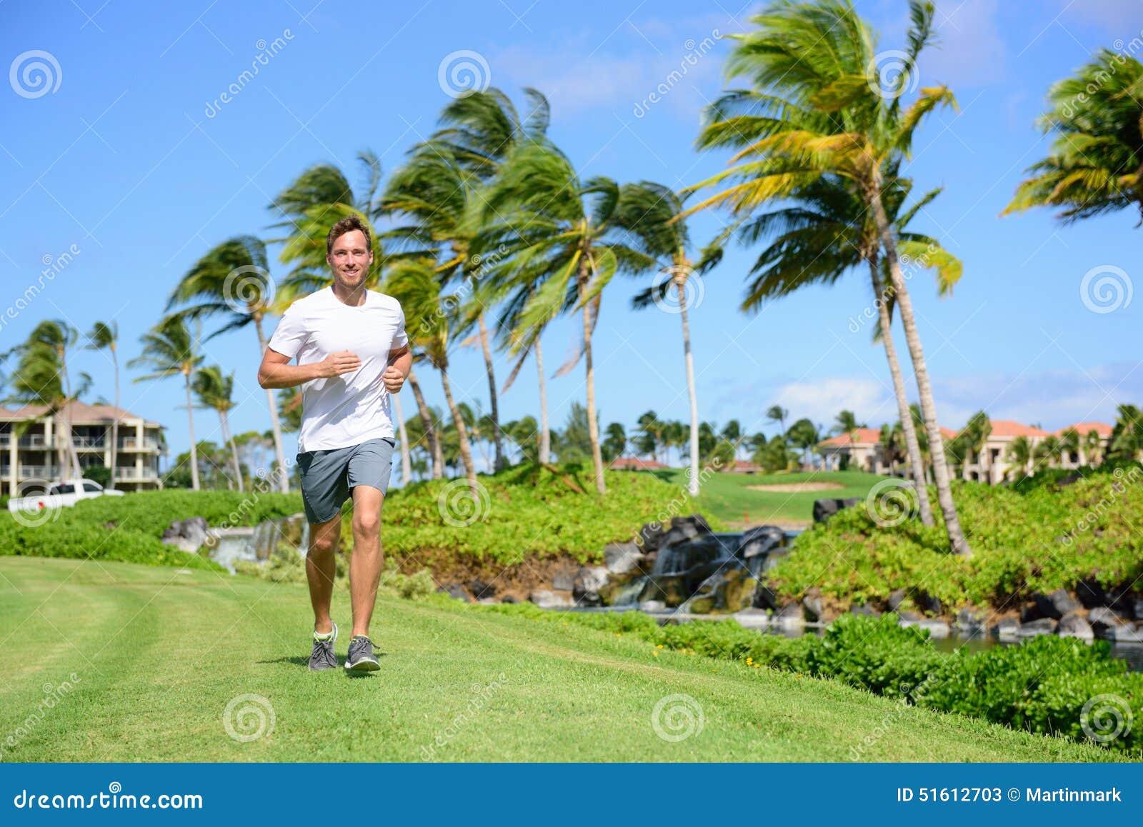 Openluchtoefeningsmens die op gras in stadspark lopen