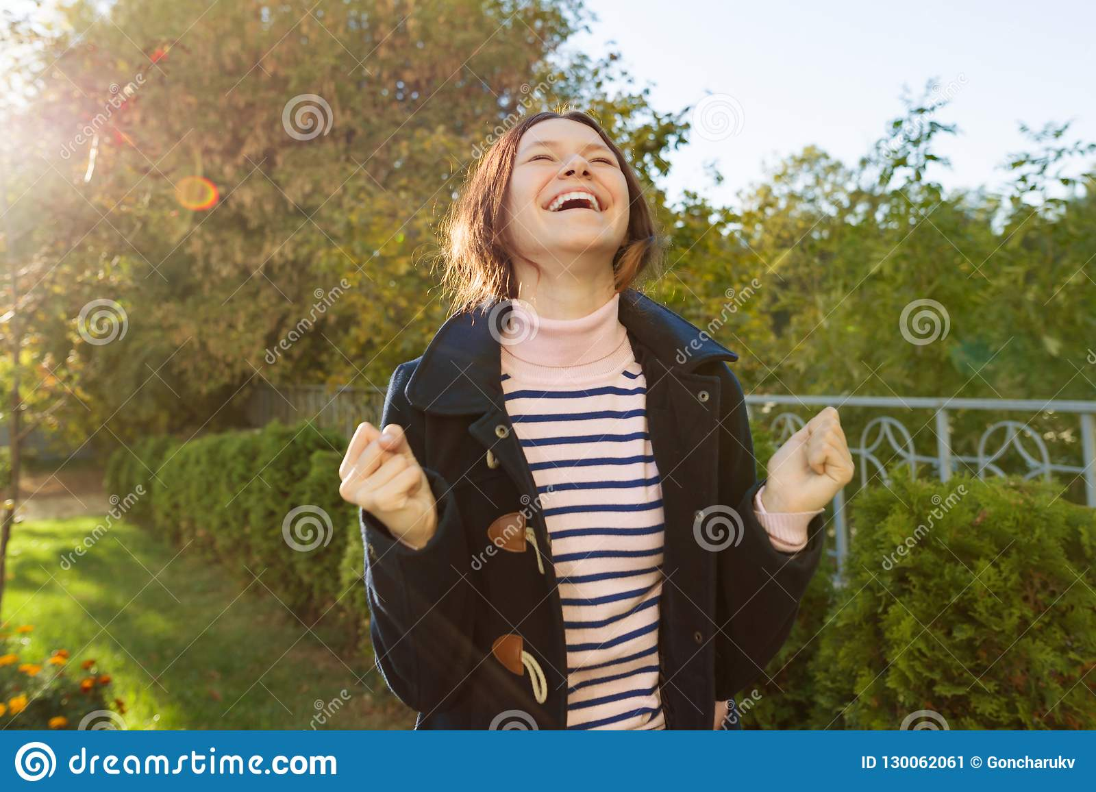 Openluchtportret van een jong tienermeisje met een emotie van geluk, succes, overwinning, gouden uur