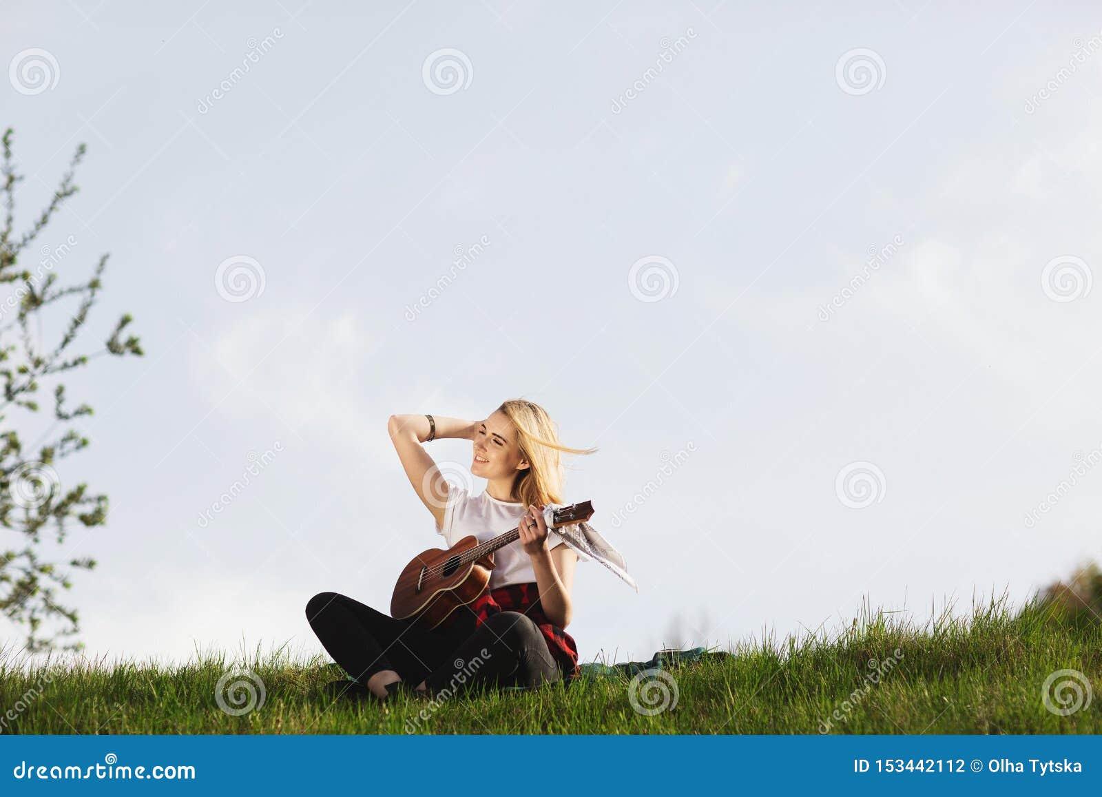Openluchtportret van een jonge mooie vrouw in zwarte hoed, het spelen gitaar Ruimte voor tekst
