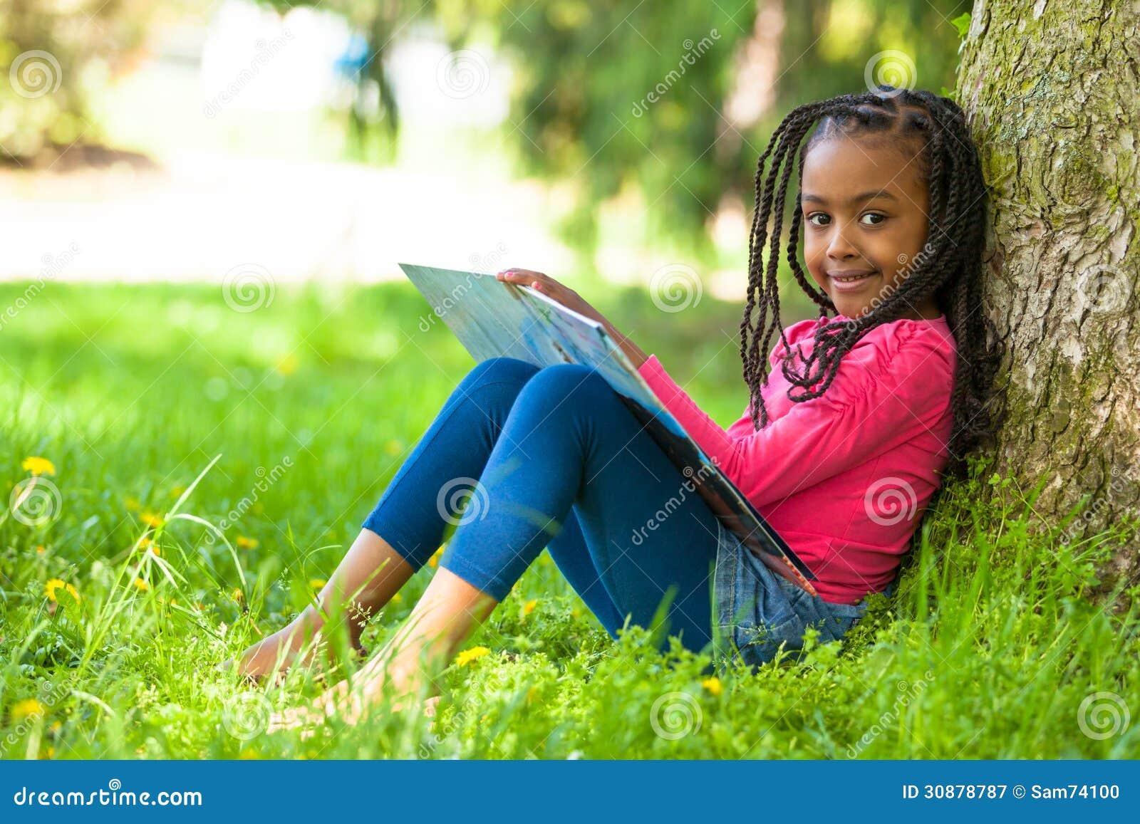 Openluchtportret van een leuk jong zwart meisje die een boe-geroep lezen