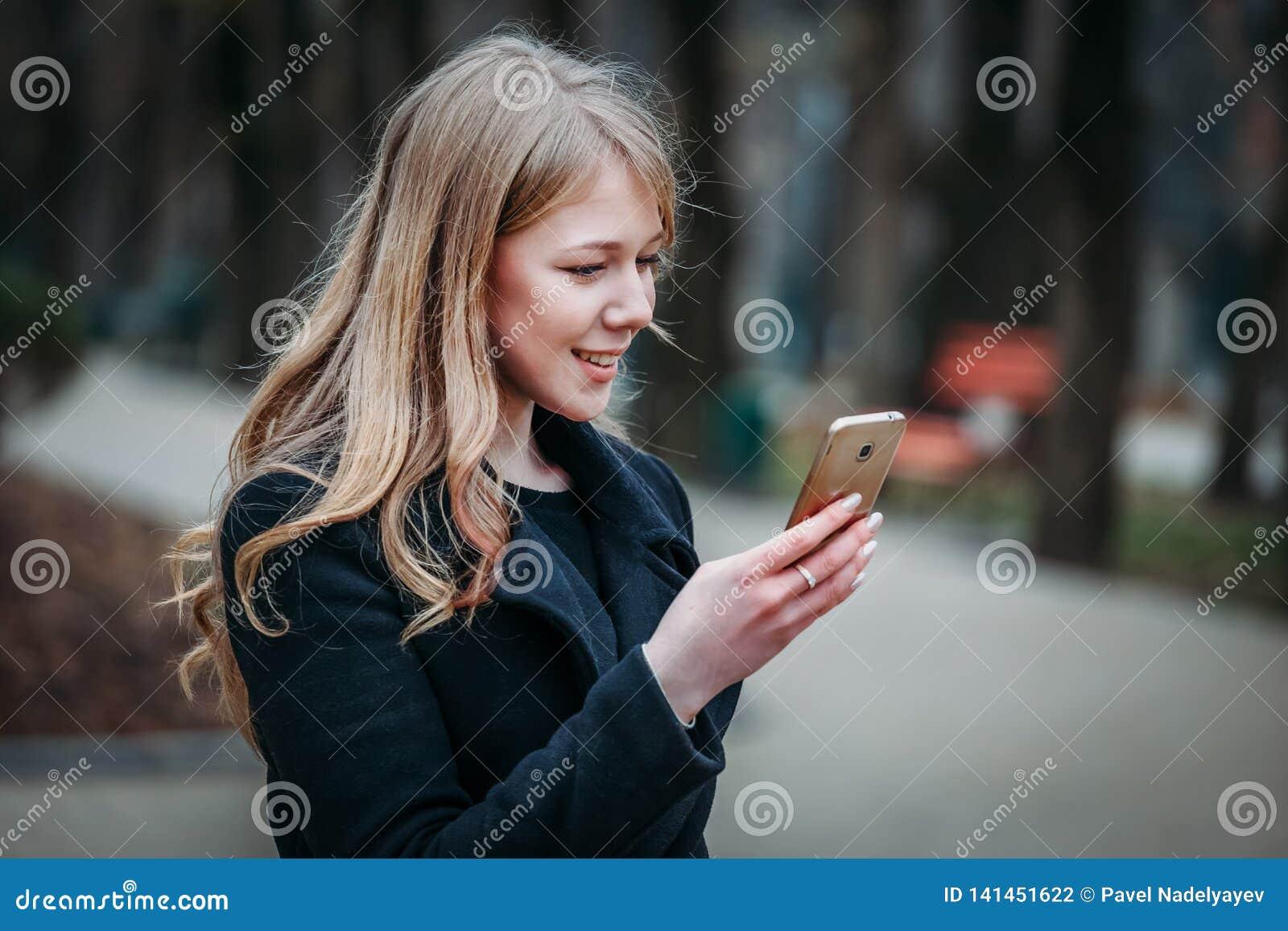 Openluchtportret van een romantische, vrij elegante bedrijfs langharige vrouw, die van een wandeling genieten door de stad met ee