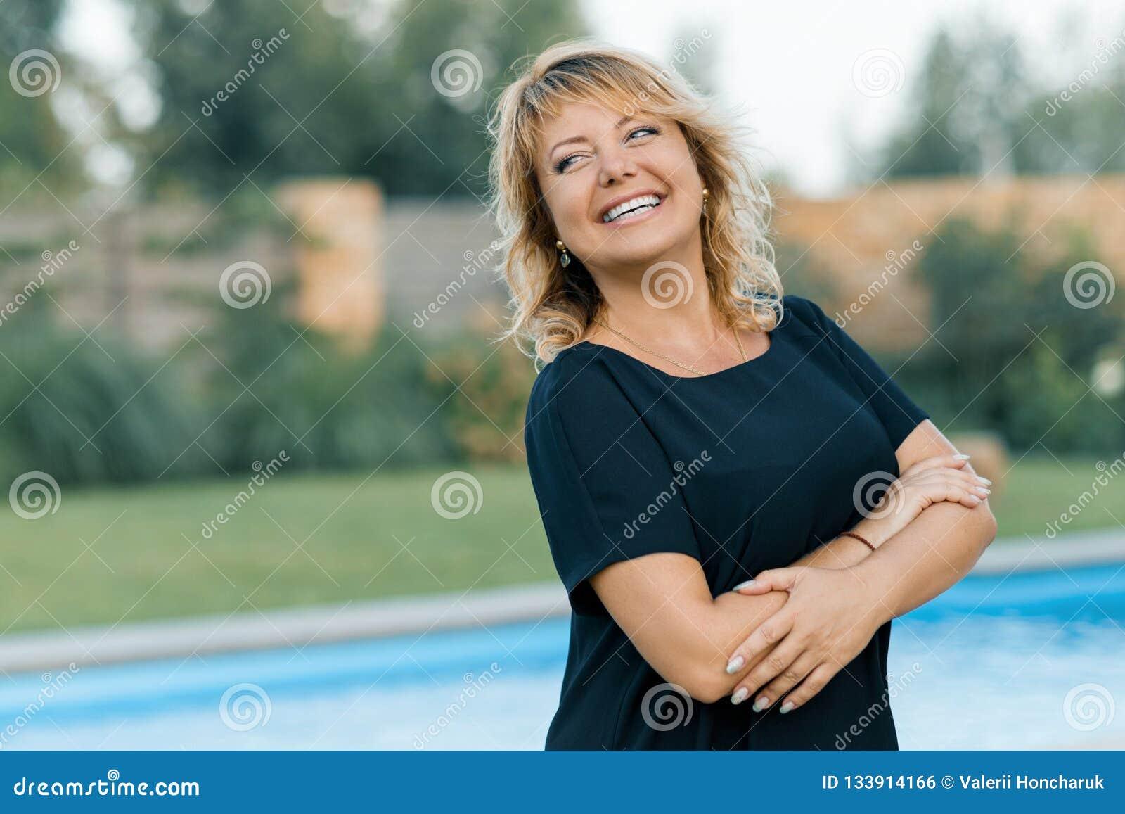 Openluchtportret van positieve zekere rijpe vrouw Glimlachend vrouwelijk blonde met gekruiste wapens, privé achtergrond van pool,