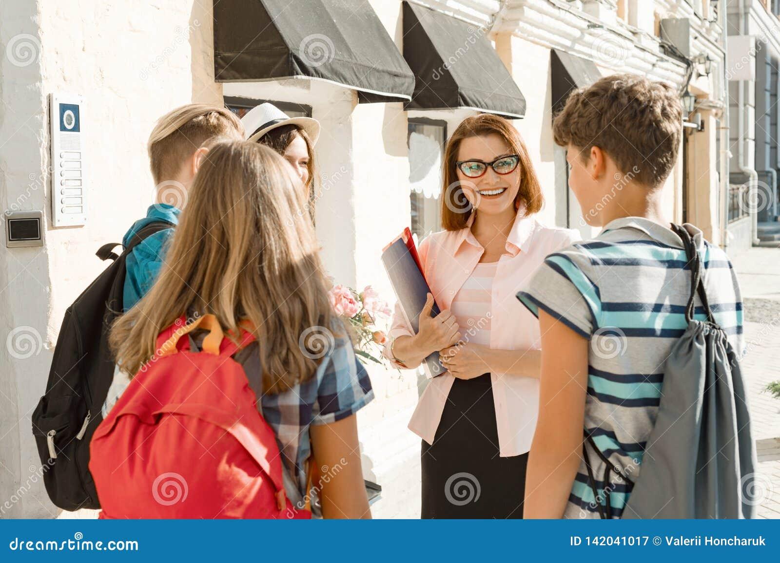 Openluchtschoolleraar met groep tienermiddelbare schoolstudenten, glimlachende leraar die aan kinderen spreken