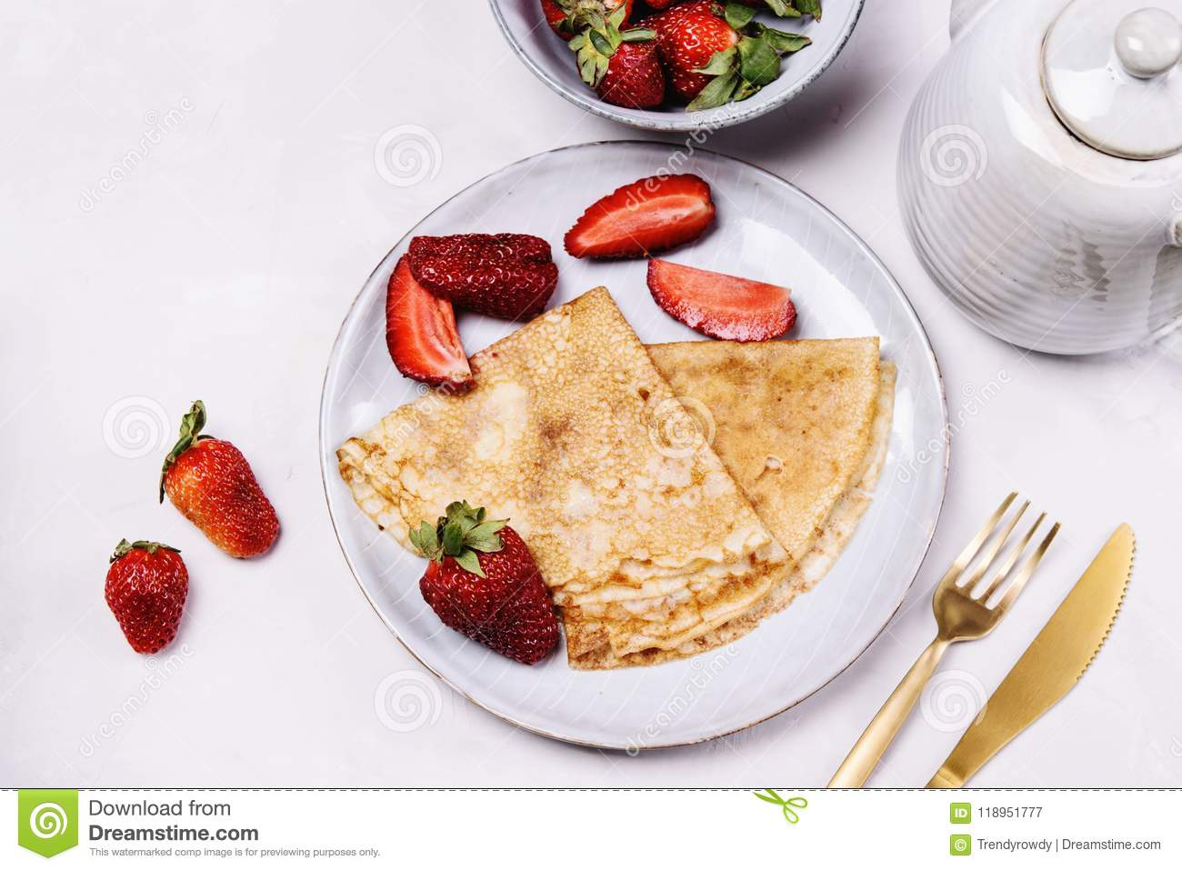 Openwork thin cheese crepes served with strawberry on grey concrete background