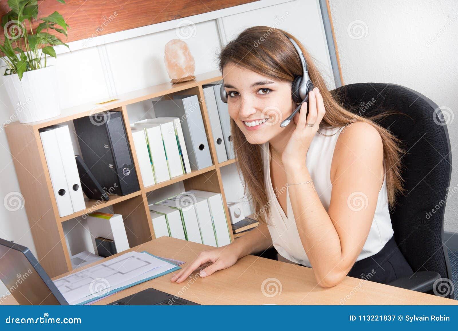 Operador de centro atrativo feliz da chamada da jovem mulher ou auriculares vestindo da menina do recepcionista