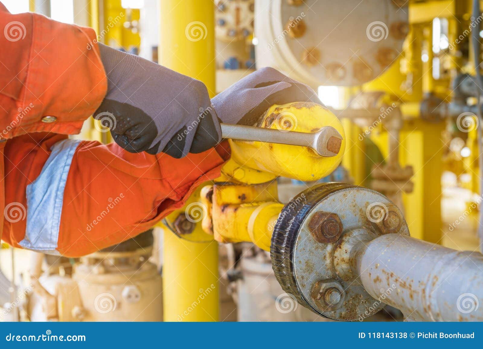 Operador de la producción que ajusta el regulador de presión del sistema de suministro de gas del instrumento en la plataforma co