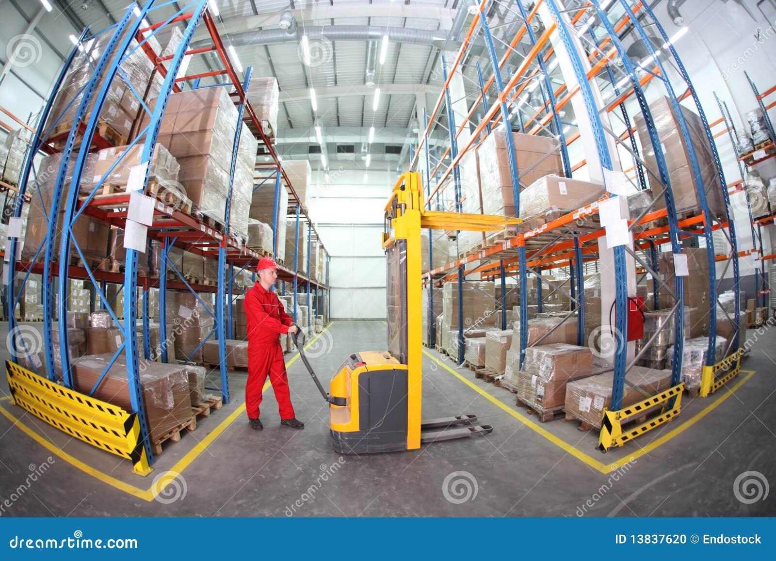 Operador manual de la carretilla elevadora en el trabajo en almacén